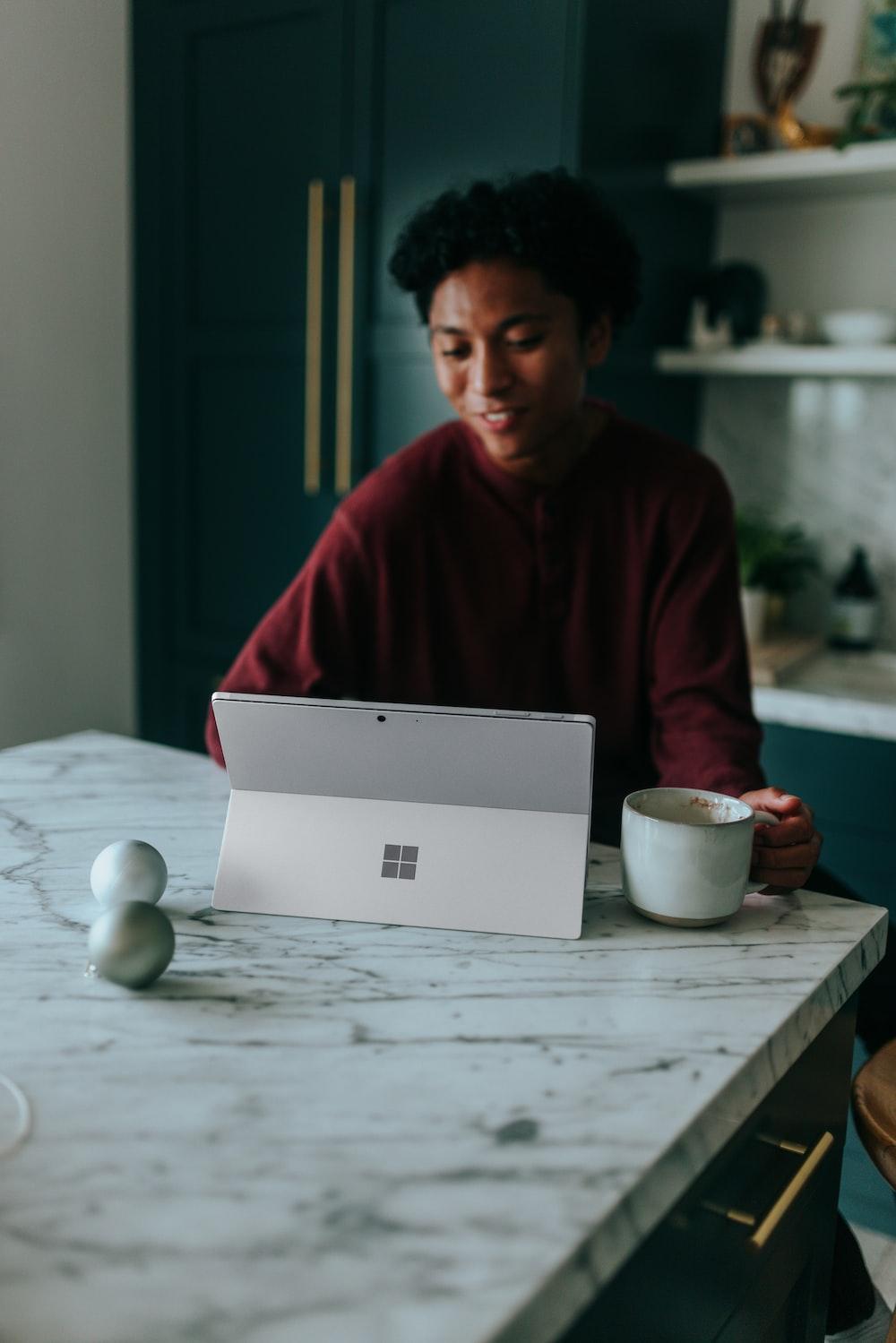 Man sitting at kitchen table watching something on his Surface laptop drinking coffee