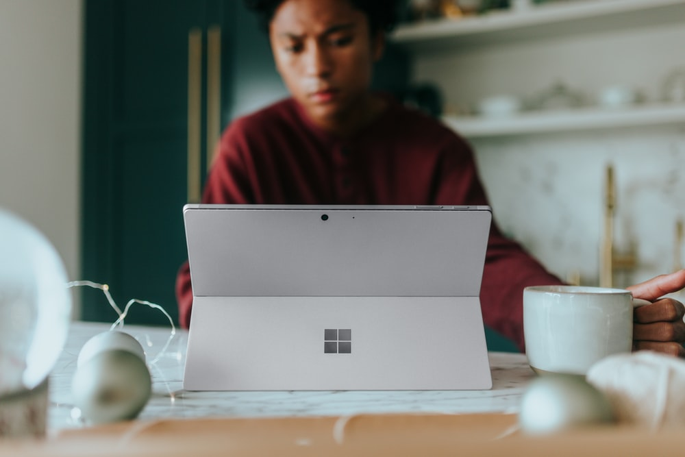 Man on his Surface laptop at home with Christmas decorations around