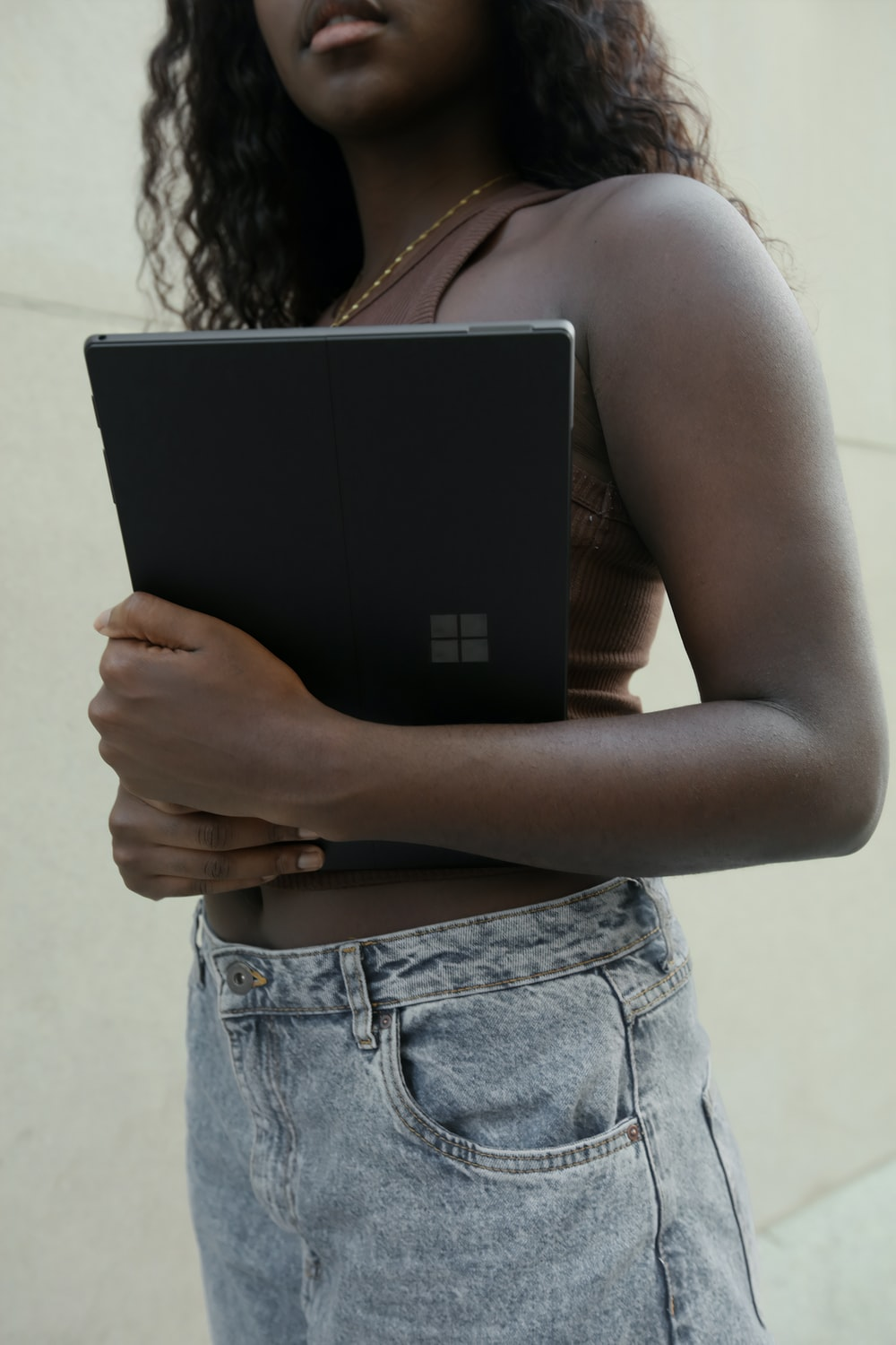 Female holding a black Surface laptop