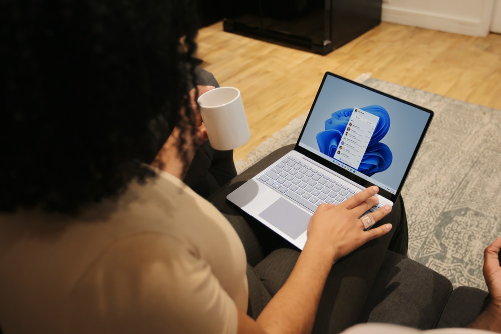 Female on her Microsoft laptop at work drinking coffee