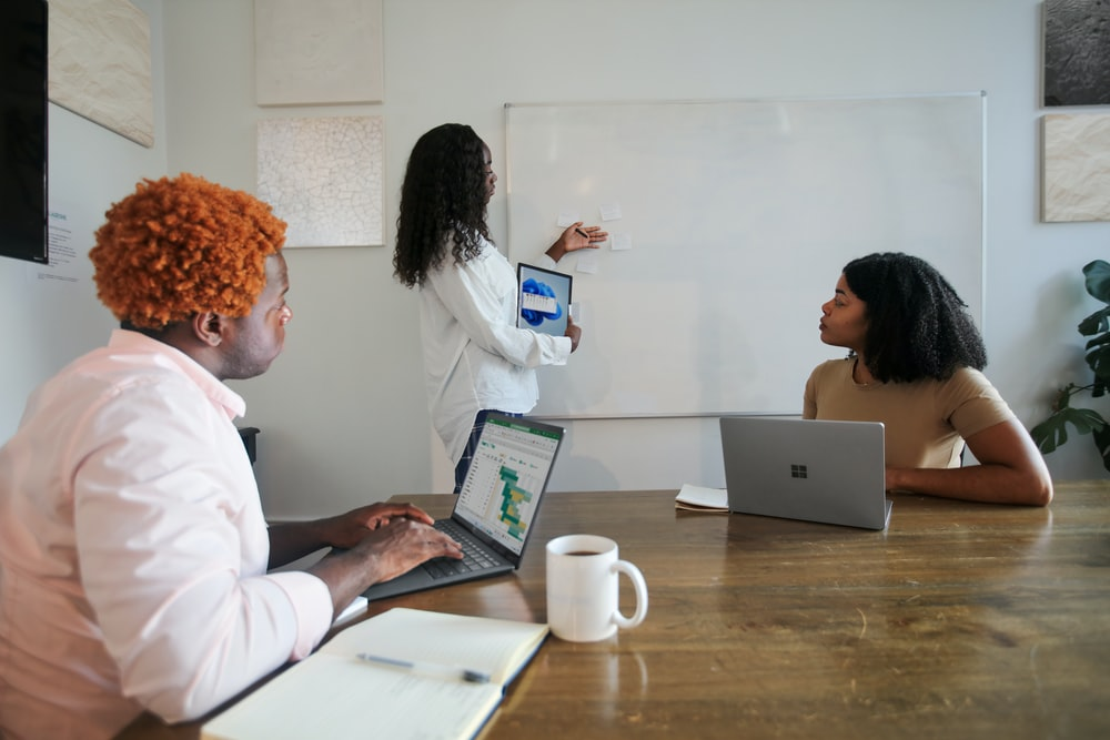 Three people in an office working with their Microsoft laptops