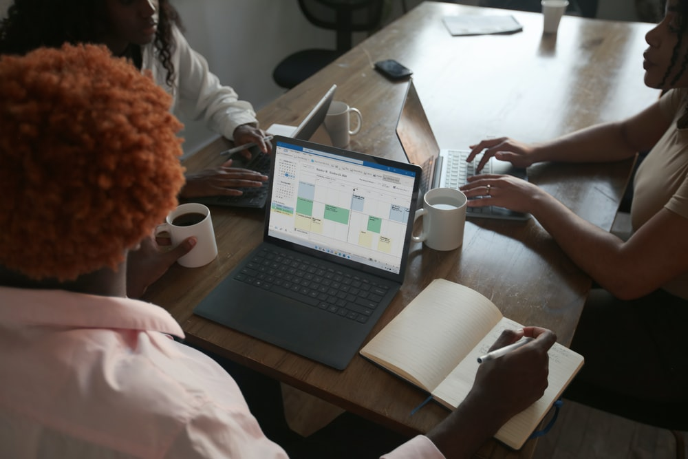 Three people in a meeting at a table discussing schedule on their Microsoft laptop