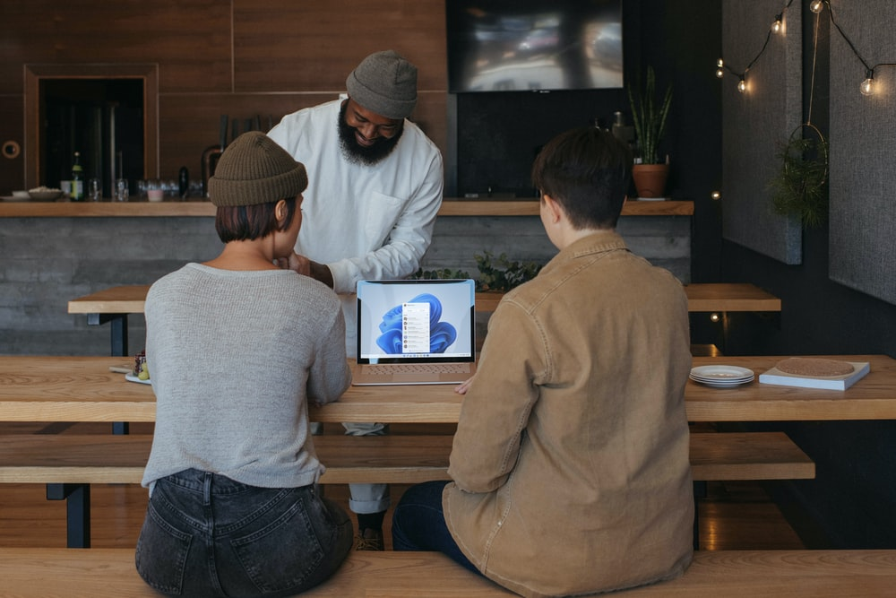 Three people sitting on benches at work around a Microsoft laptop