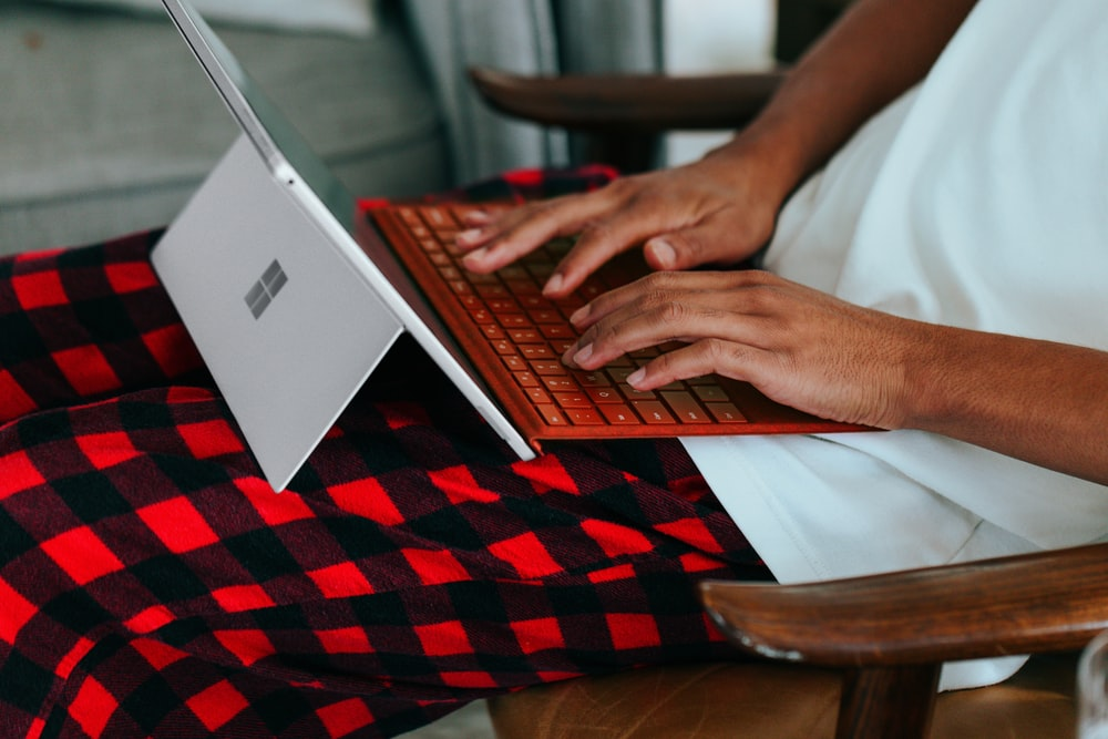 Person in checkered pajamas on their Surface laptop at home