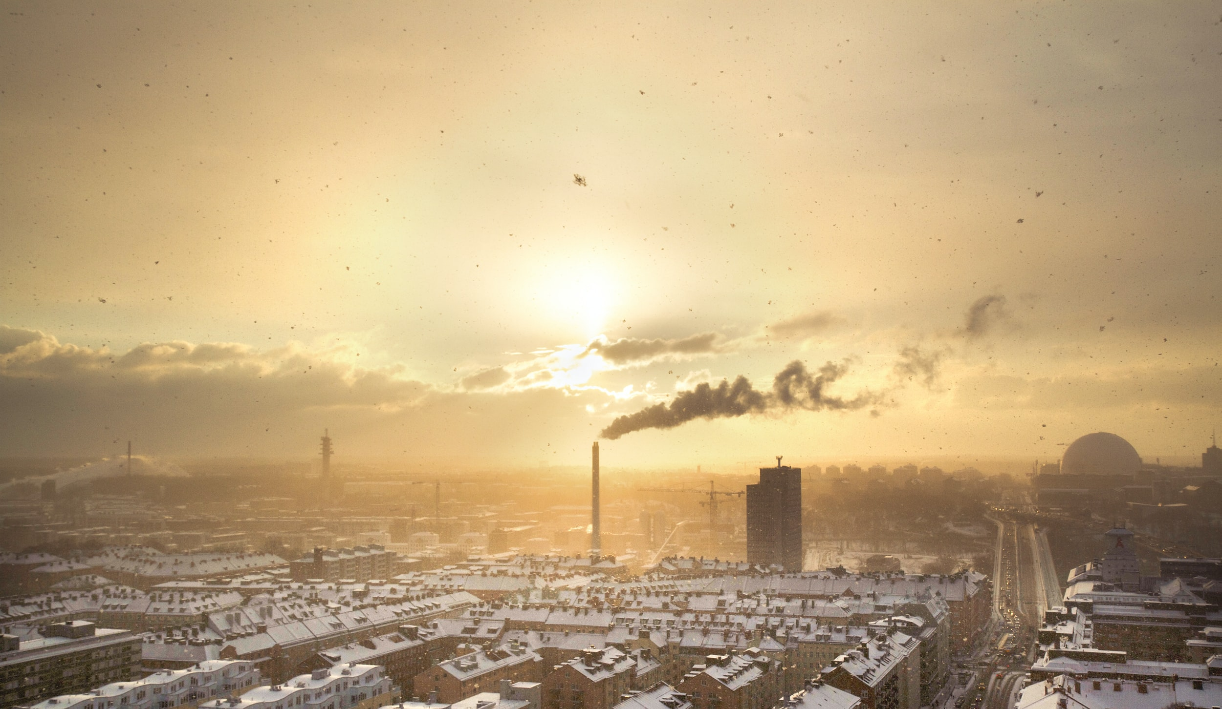 An industrial cityscape of a town filled with factories and air pollution at sunset