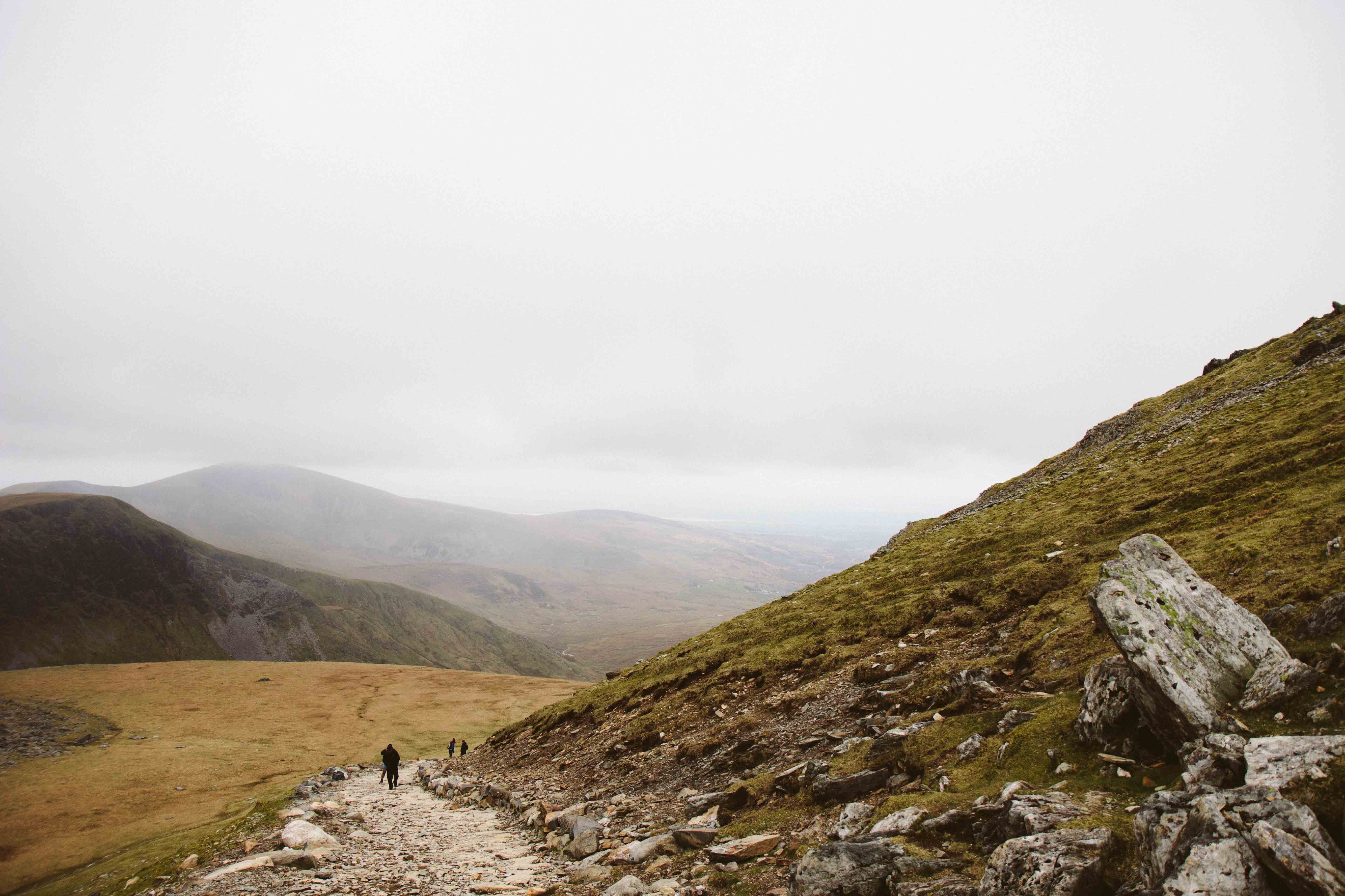Hikers climbing up a rocky path at the foot of a green hill on a cloudy day