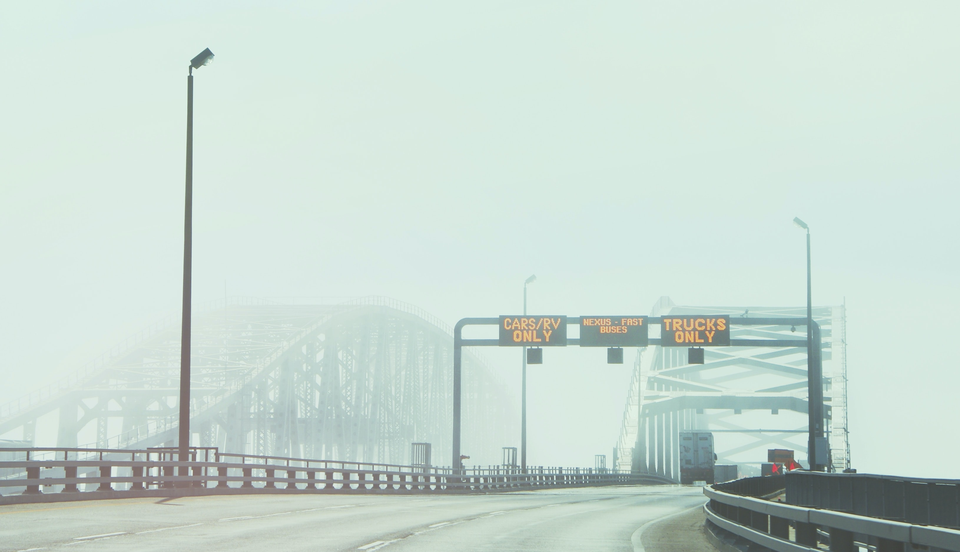 Two bridges in the fog with a highway sign