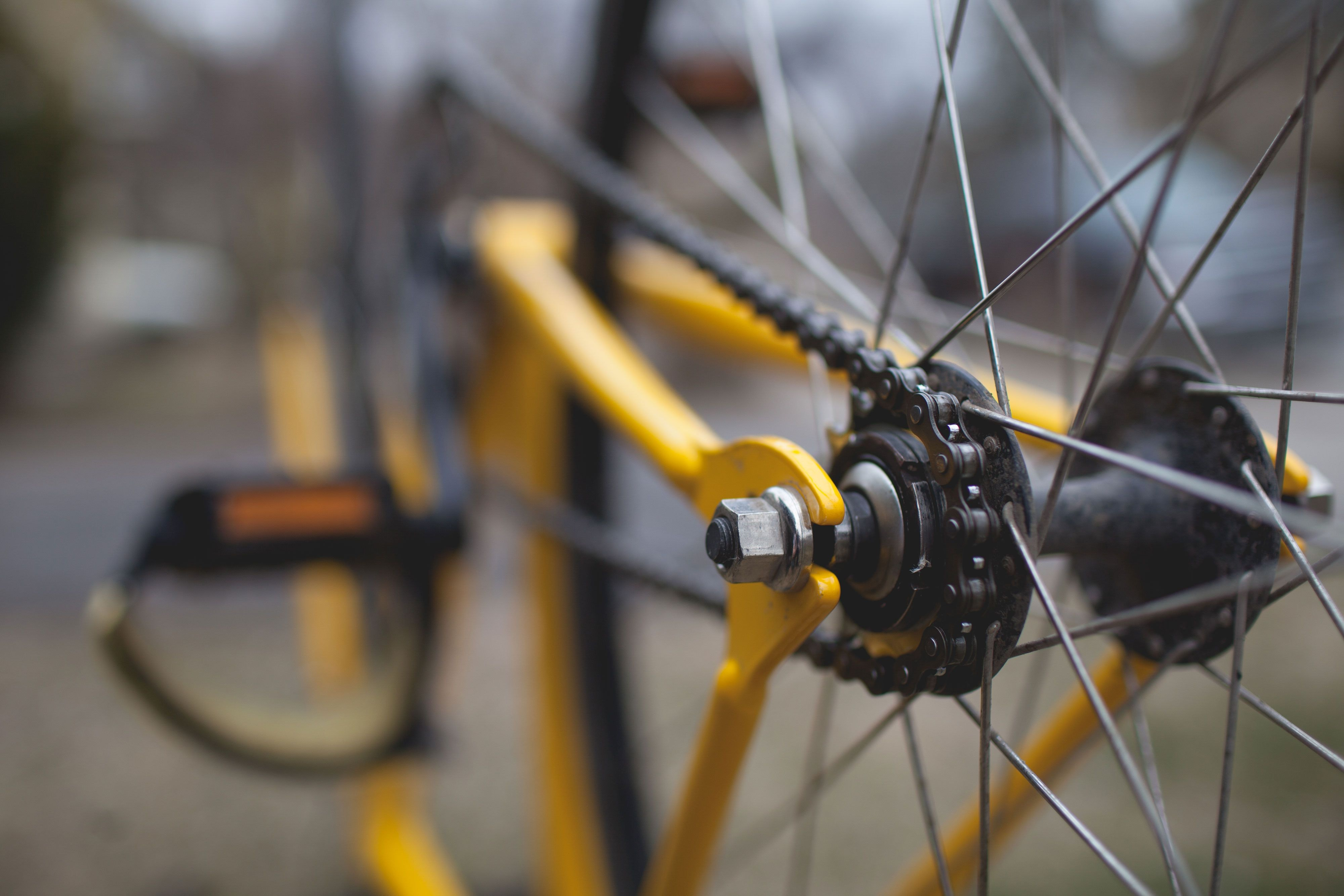 A close up of a yellow bike, emphasizing its spokes, gears, and pedals