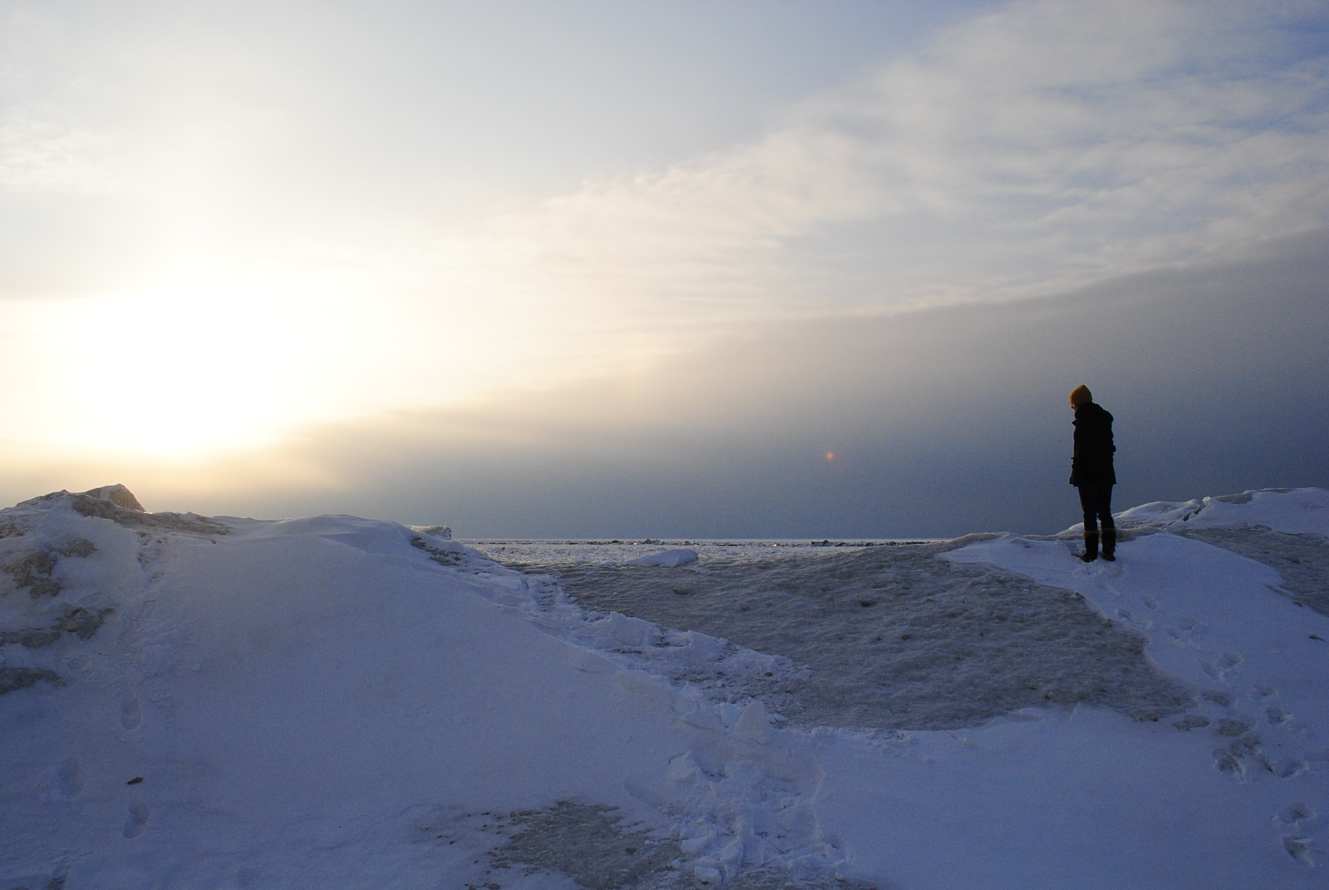 person standing on snow mountain under sunset