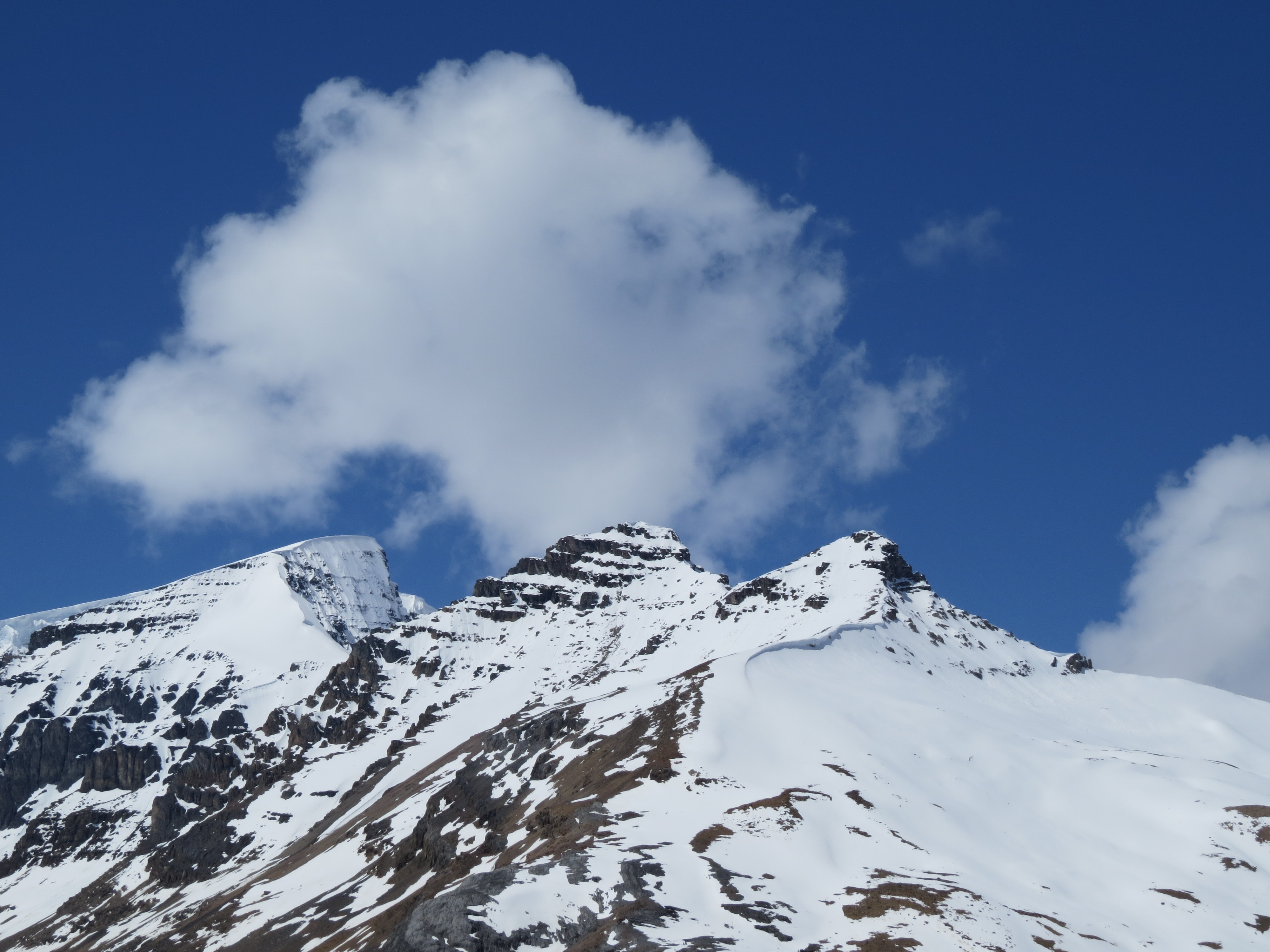Clouds over a snowy mountain peaks at Banff National Park