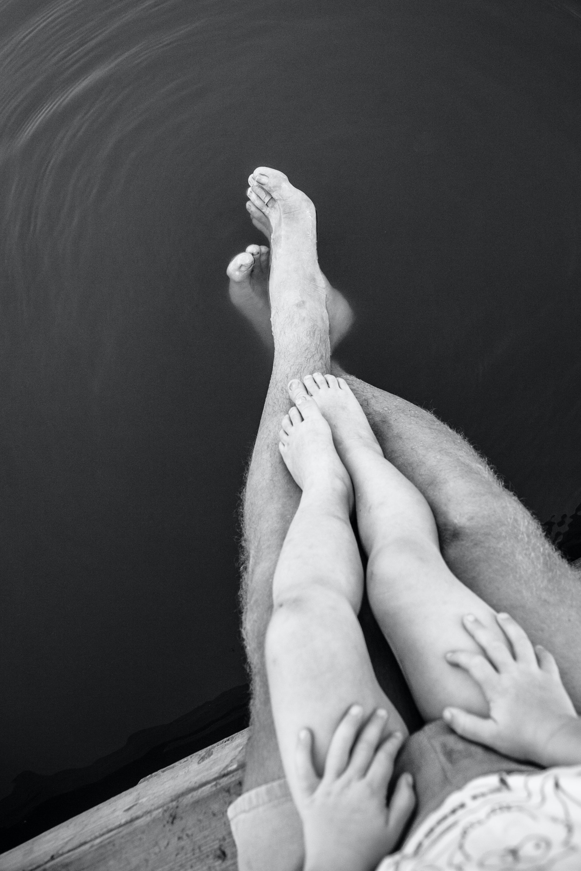 Child sits on lap of parent as their legs dangle off into the water
