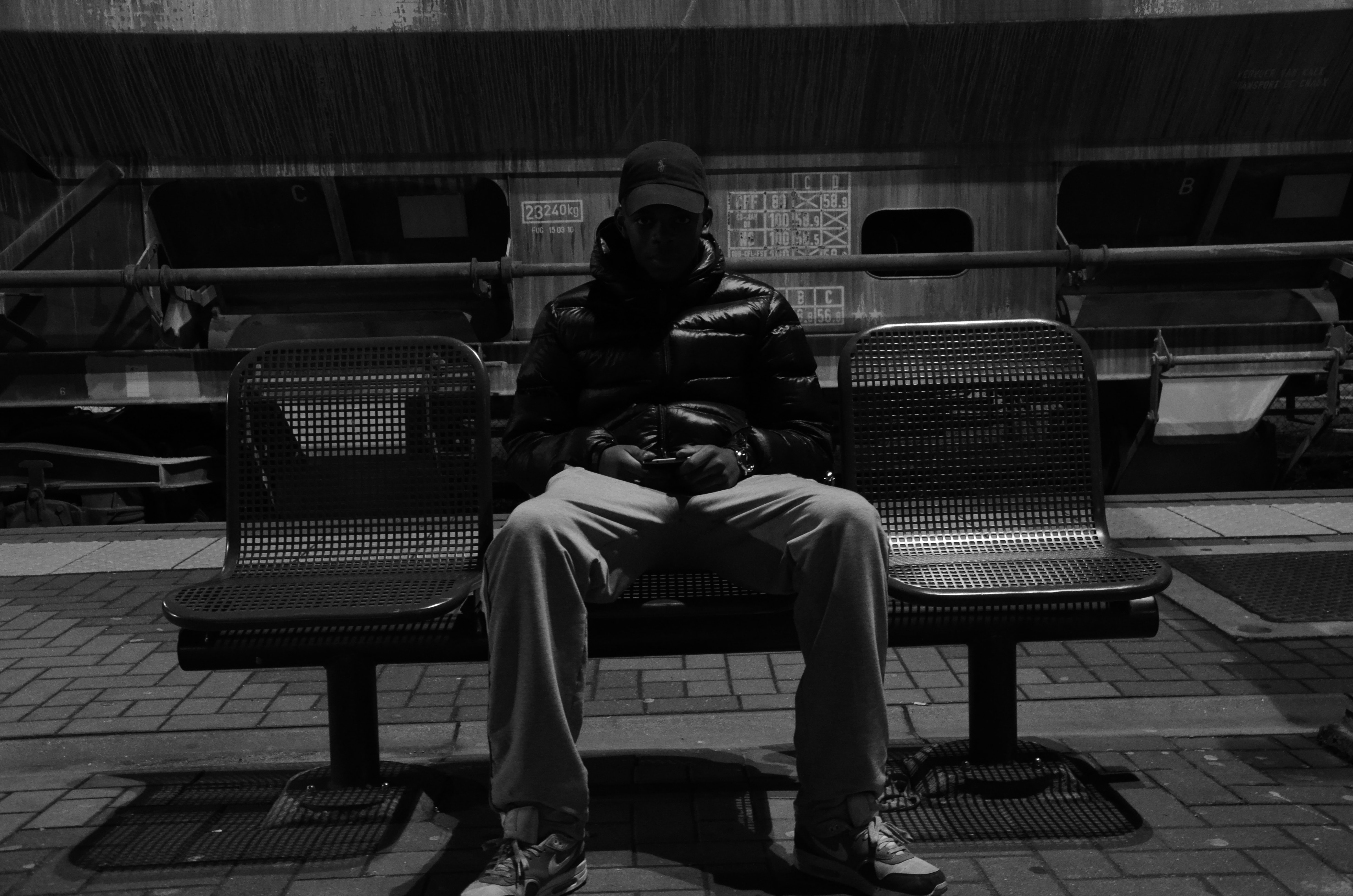 grayscale photography of man sitting down on metal bench