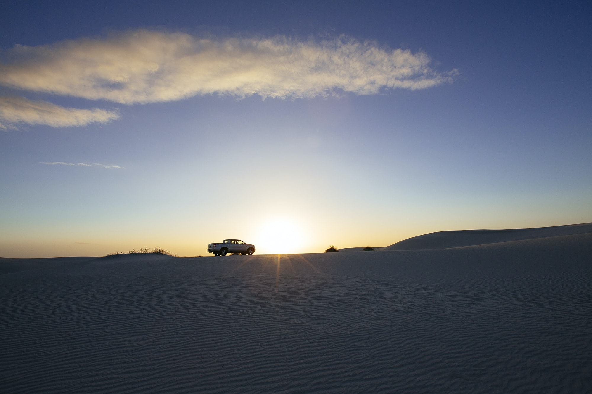 Truck silhouetted by sunset in the desert.