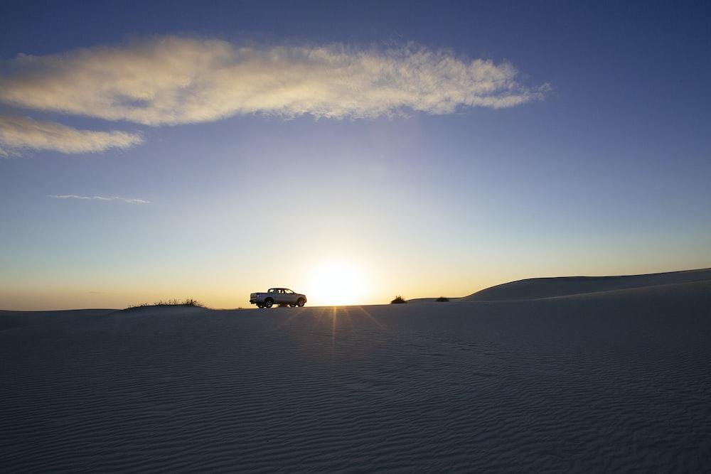 car on desert during sunset