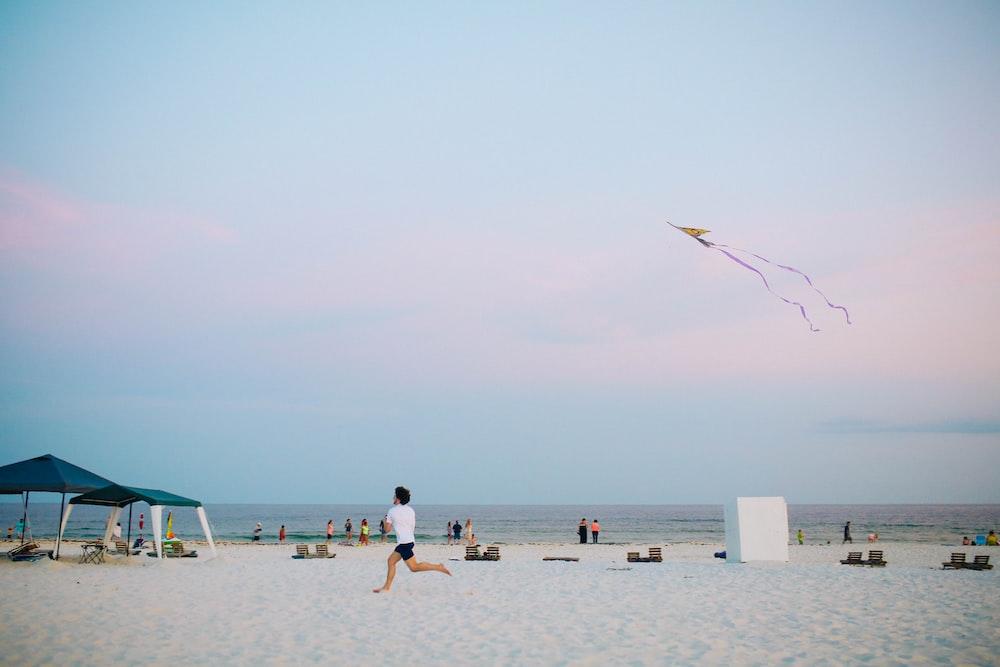 man running on white sand beach holding kite