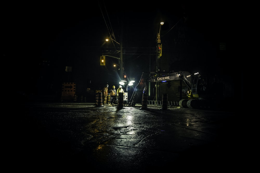 three people standing near utility post with lights turned on during nighttime