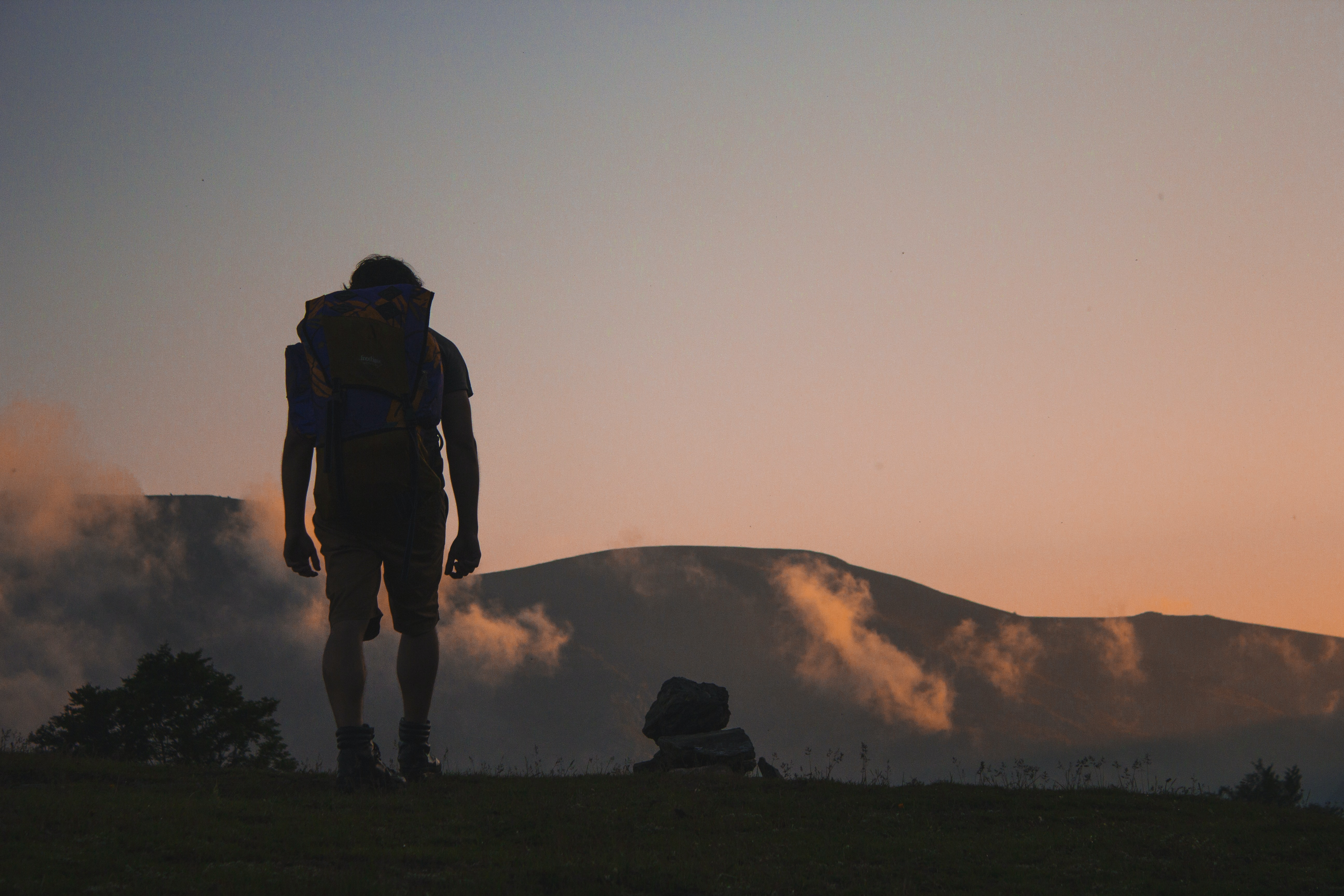 silhouette of man walking along field leading to mountain