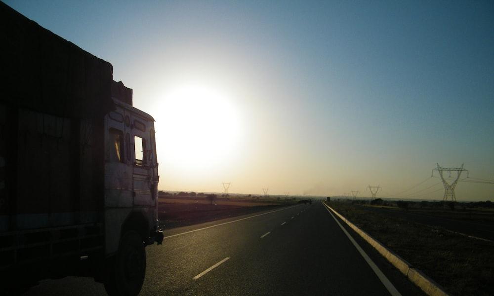 gray truck on asphalt road during sunset