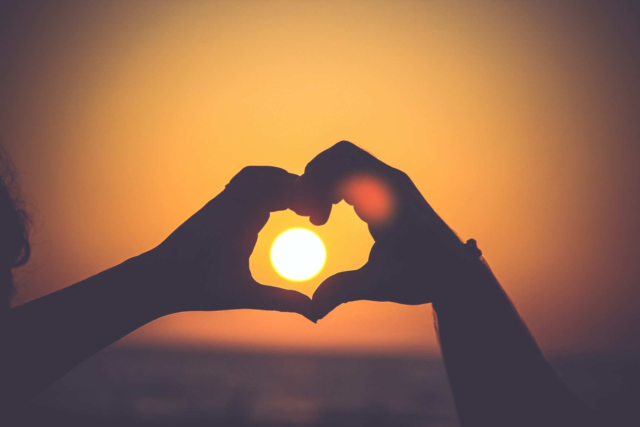 Hands in the silhouette of a heart outline the setting sun on a beach
