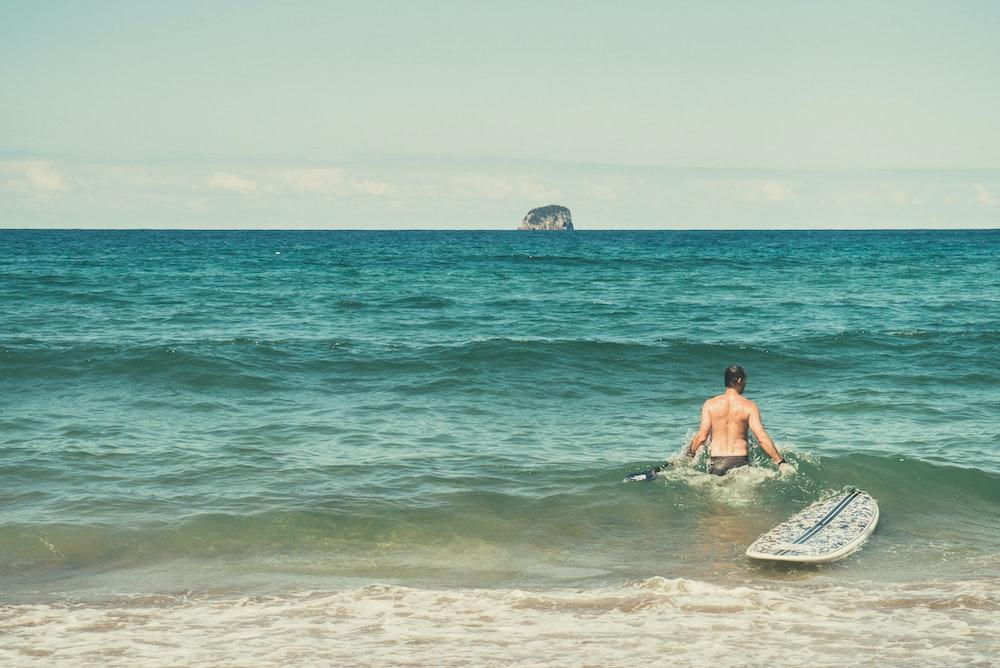 man in water beside surfboard