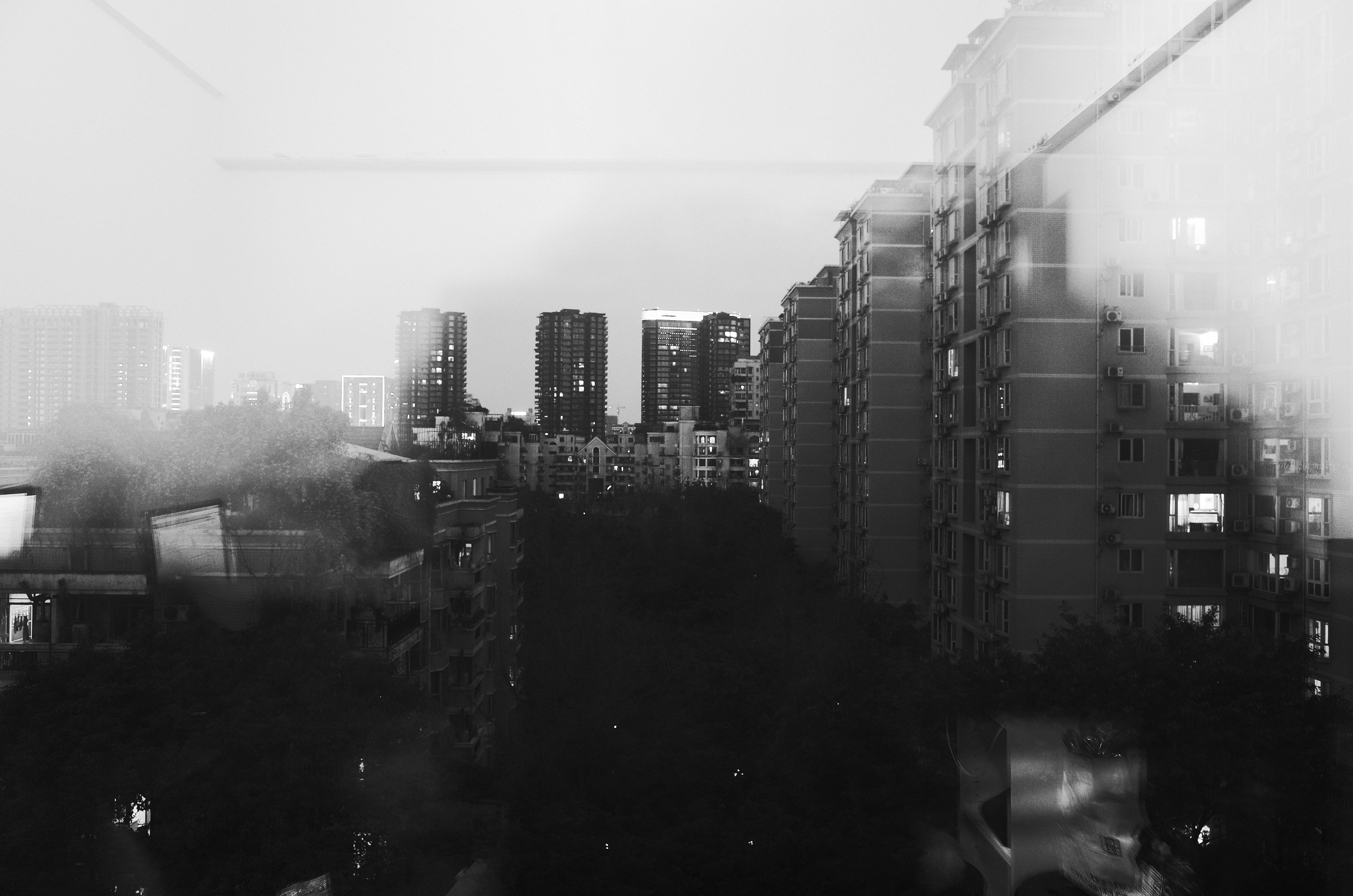 A fuzzy black-and-white shot of an apartment complex seen through a window