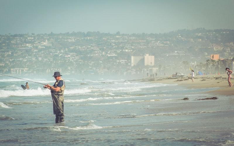 a man standing on the shallow part of the sea and using a fishing rod to fish