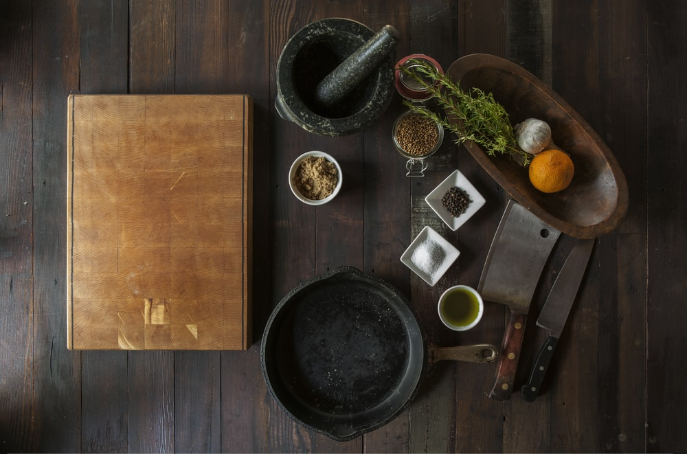 black mortar and pestle beside brown box in top view photography