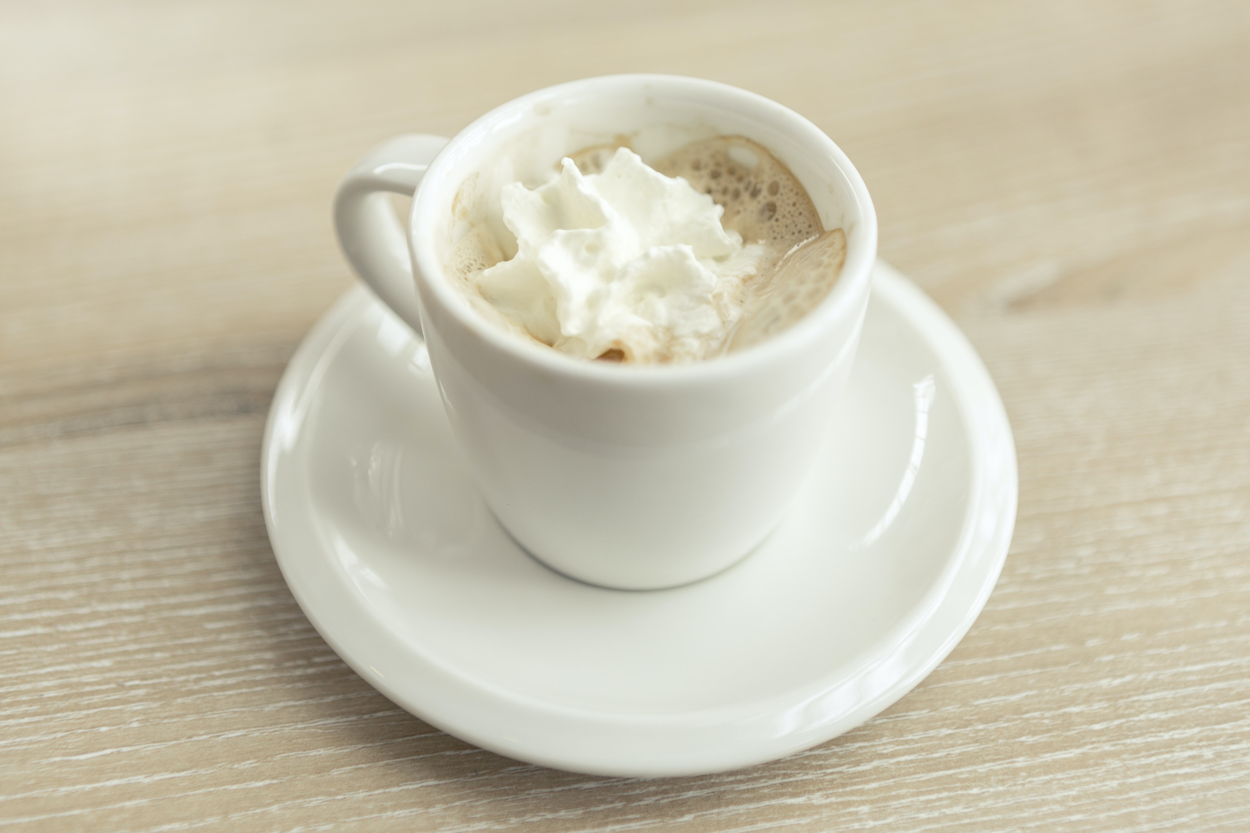 Espresso with whipped cream in a white mug on a white saucer with a light wooden table underneath