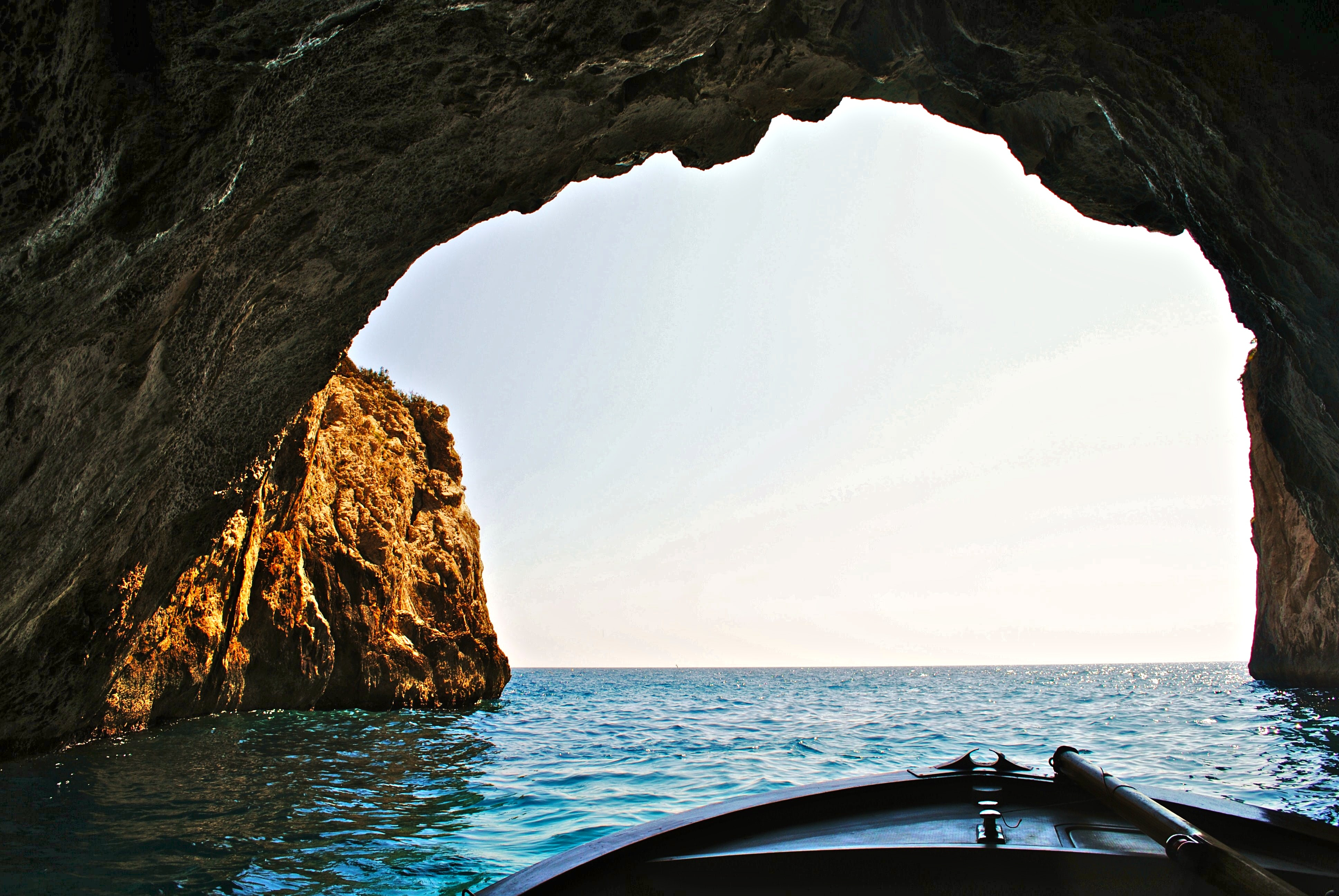 The bow of a boat on a lake inside of a cave looking out towards the opening