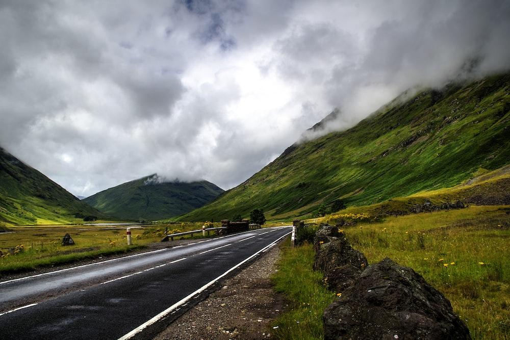 narrow road near grass and mountain