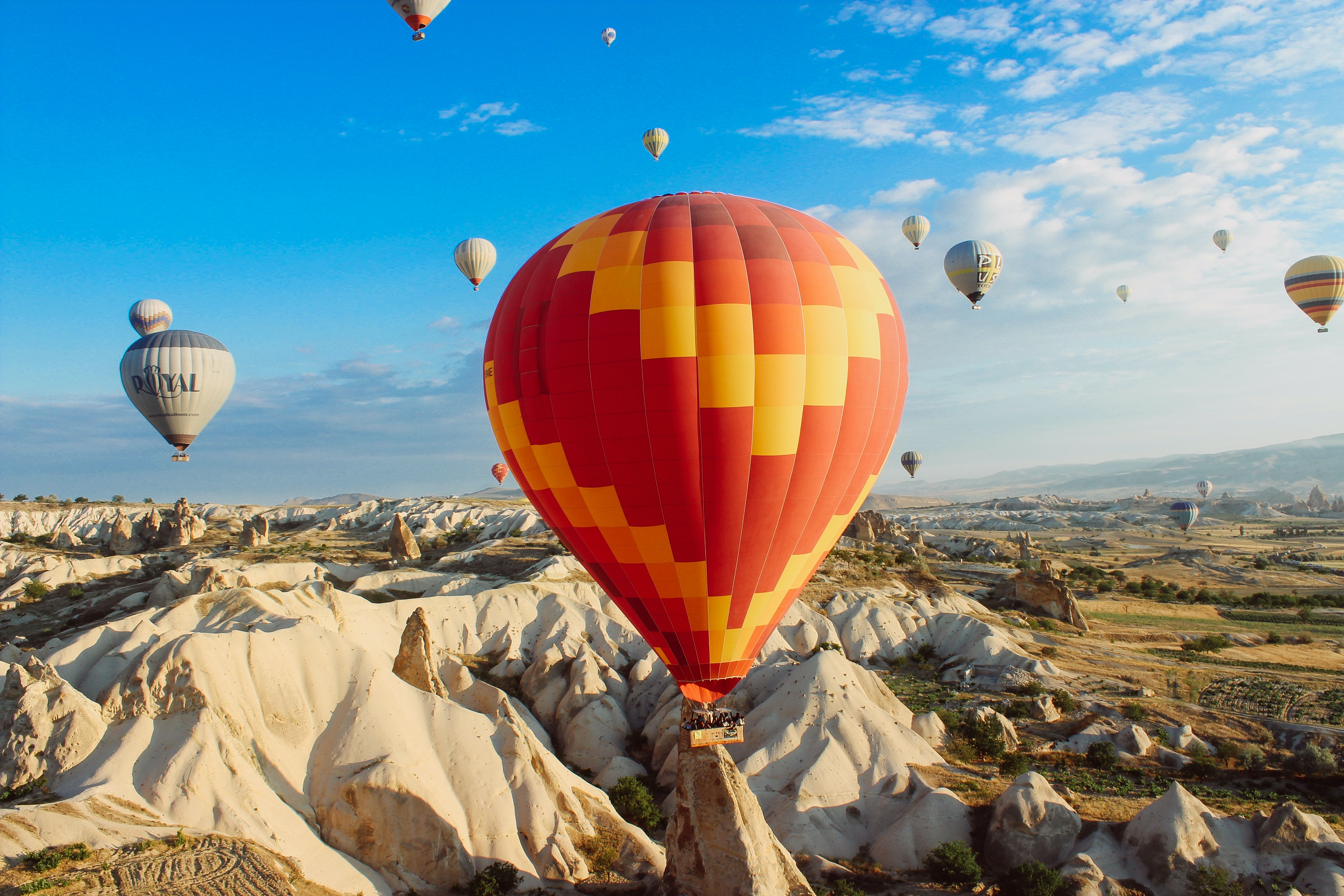 Colorful hot air balloons fly and float over a desert landscape