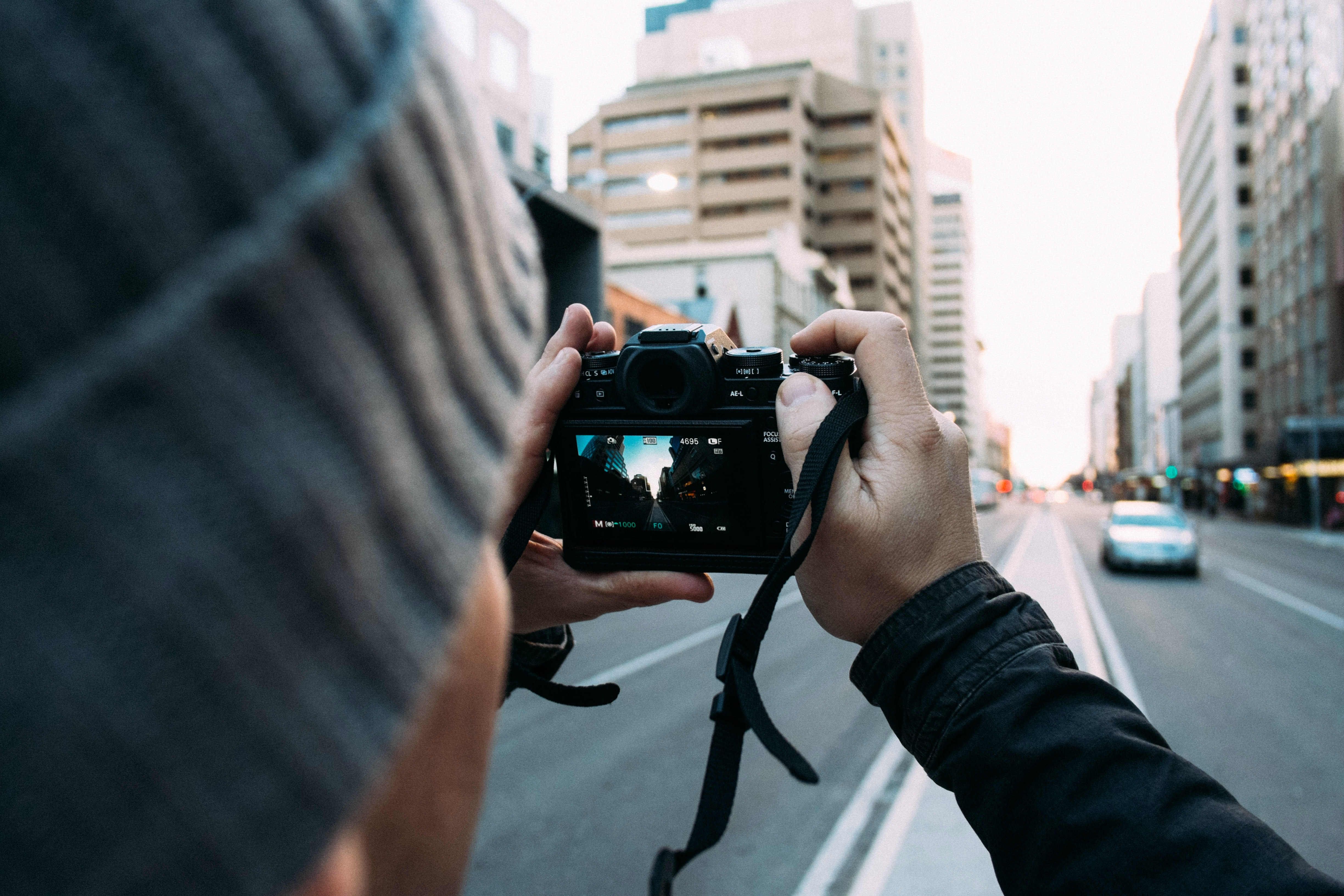 An over-the-shoulder shot of a person in a knit cap taking a photo in a city street