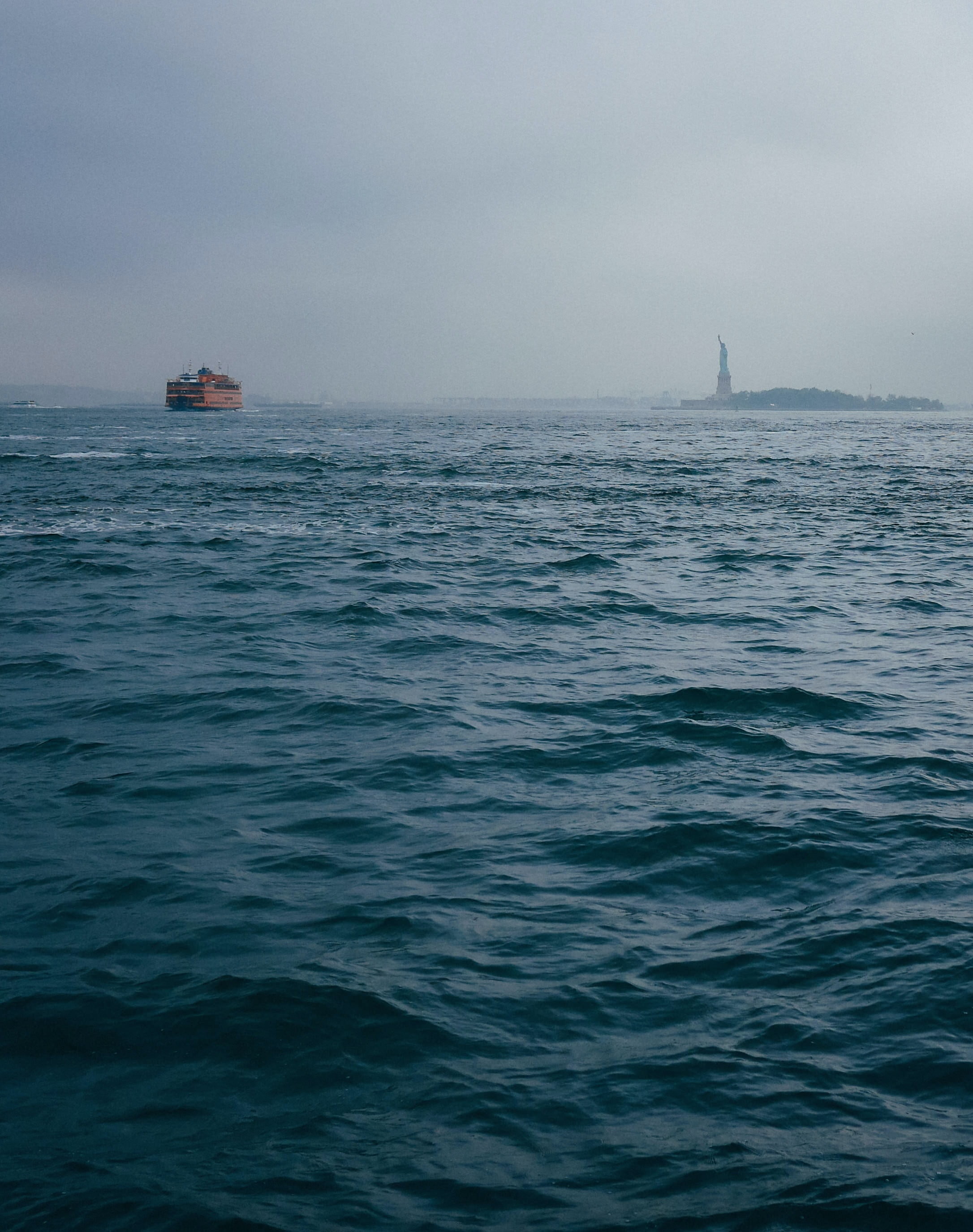The Statue of Liberty and a cargo ship from the distance on a foggy day