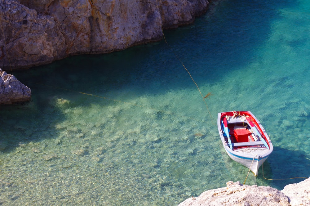 white and red boat toy docked on brown rock