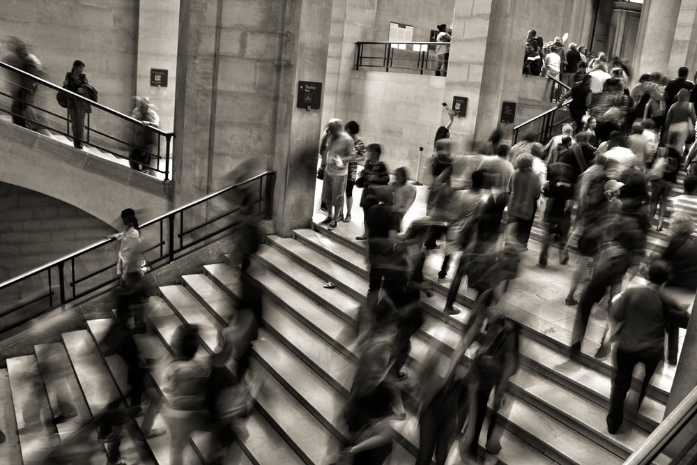 A desaturated long-exposure shot of people crowding on stairs in a large public building