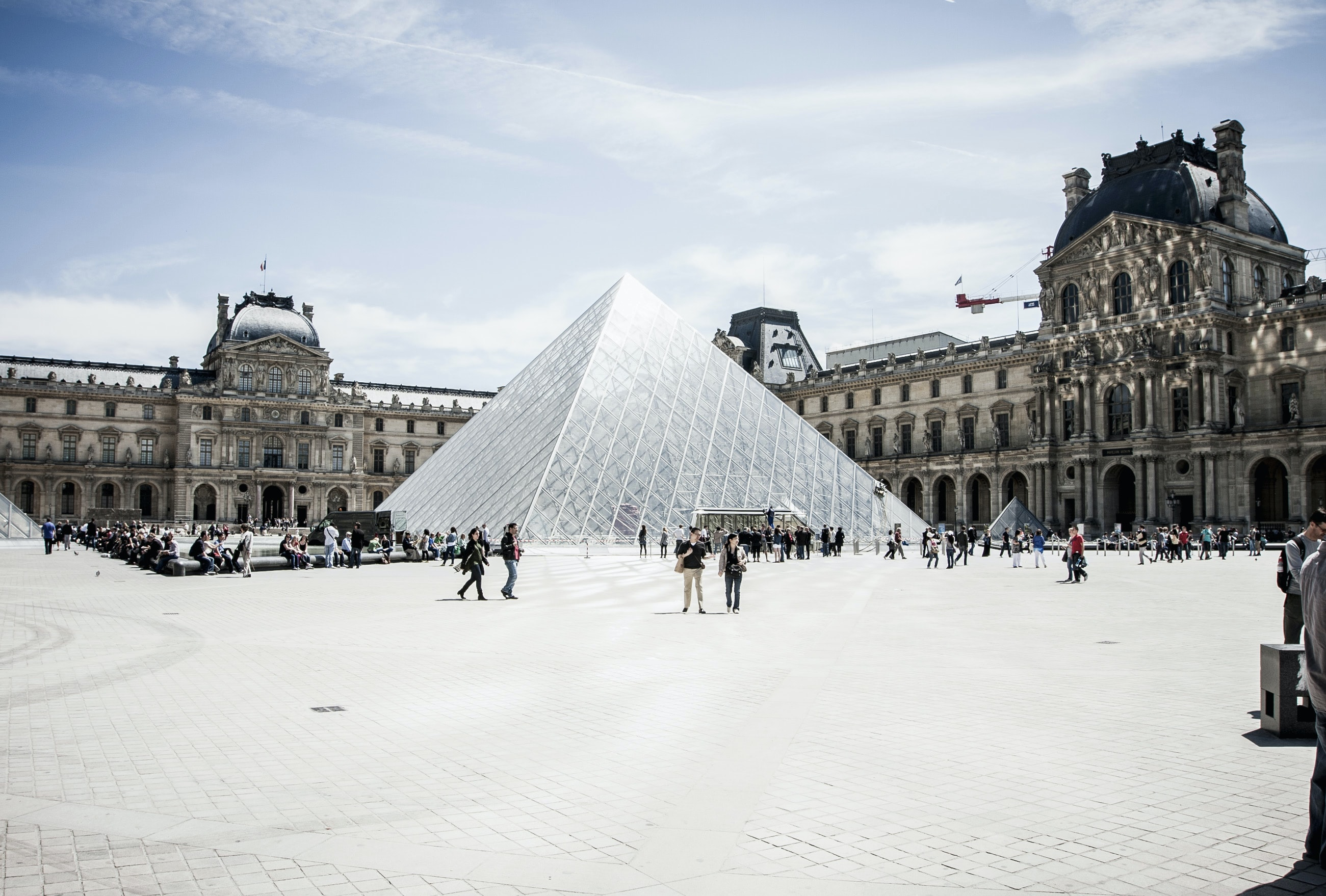 Groups of people walking in front of the glass pyramid in the Louvre courtyard in Paris