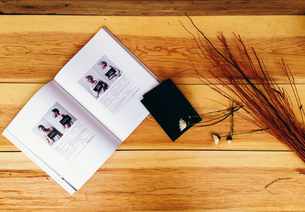 A book of headshots, a black paper, and old dried flowers on a wooden surface