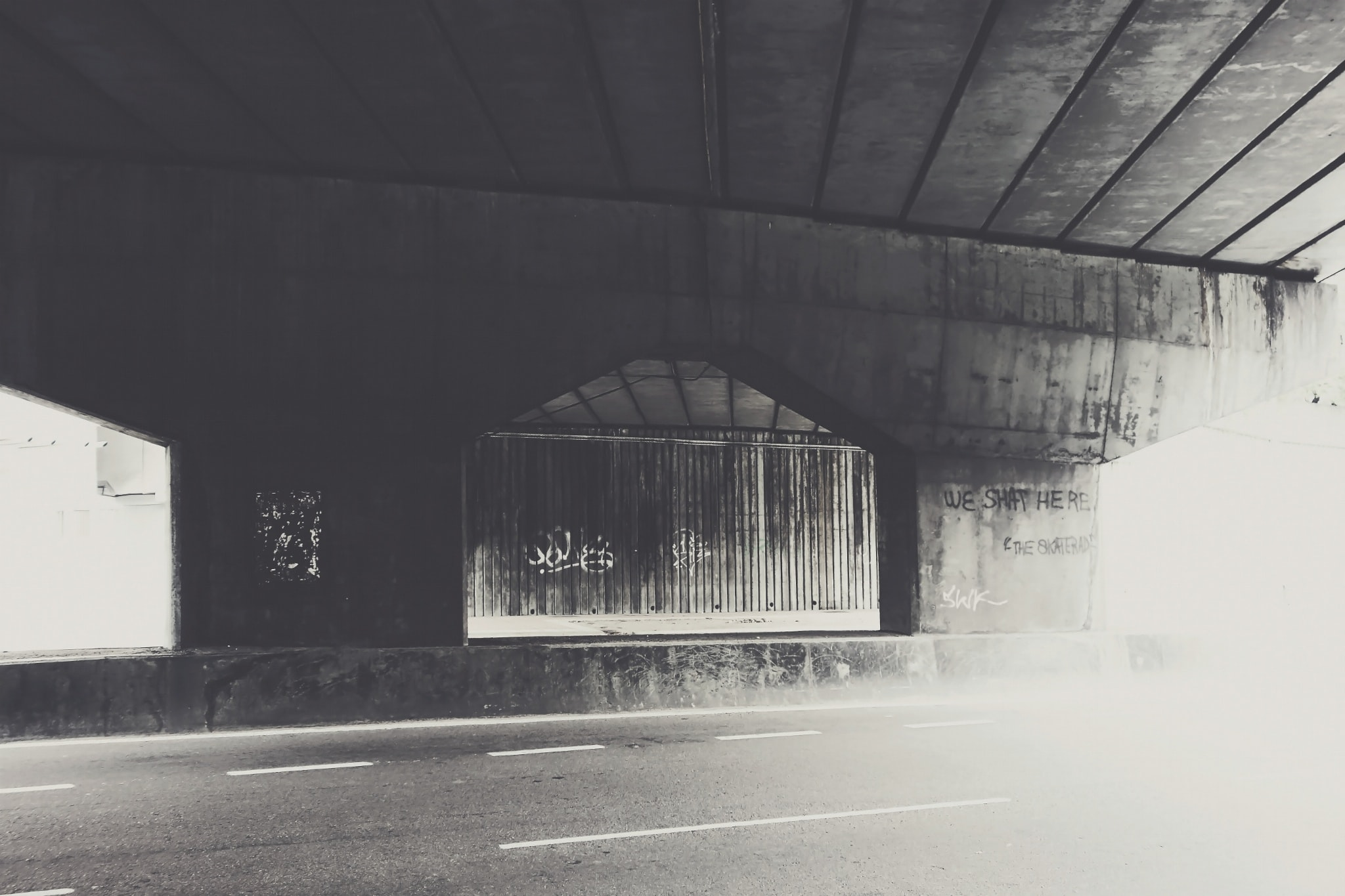 Black and white shot of underpass with graffiti and road