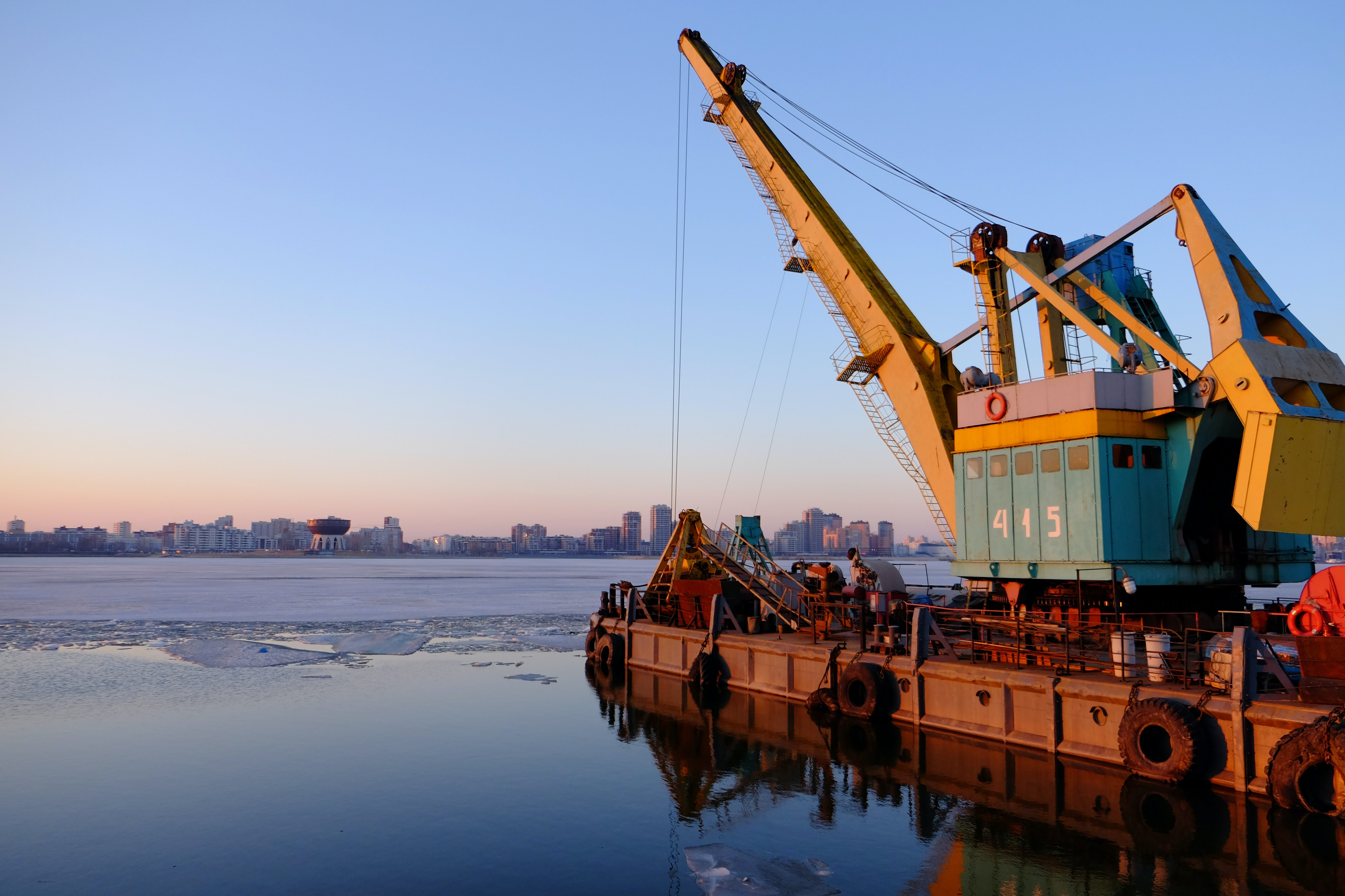 An industrial crane on a dock over the water