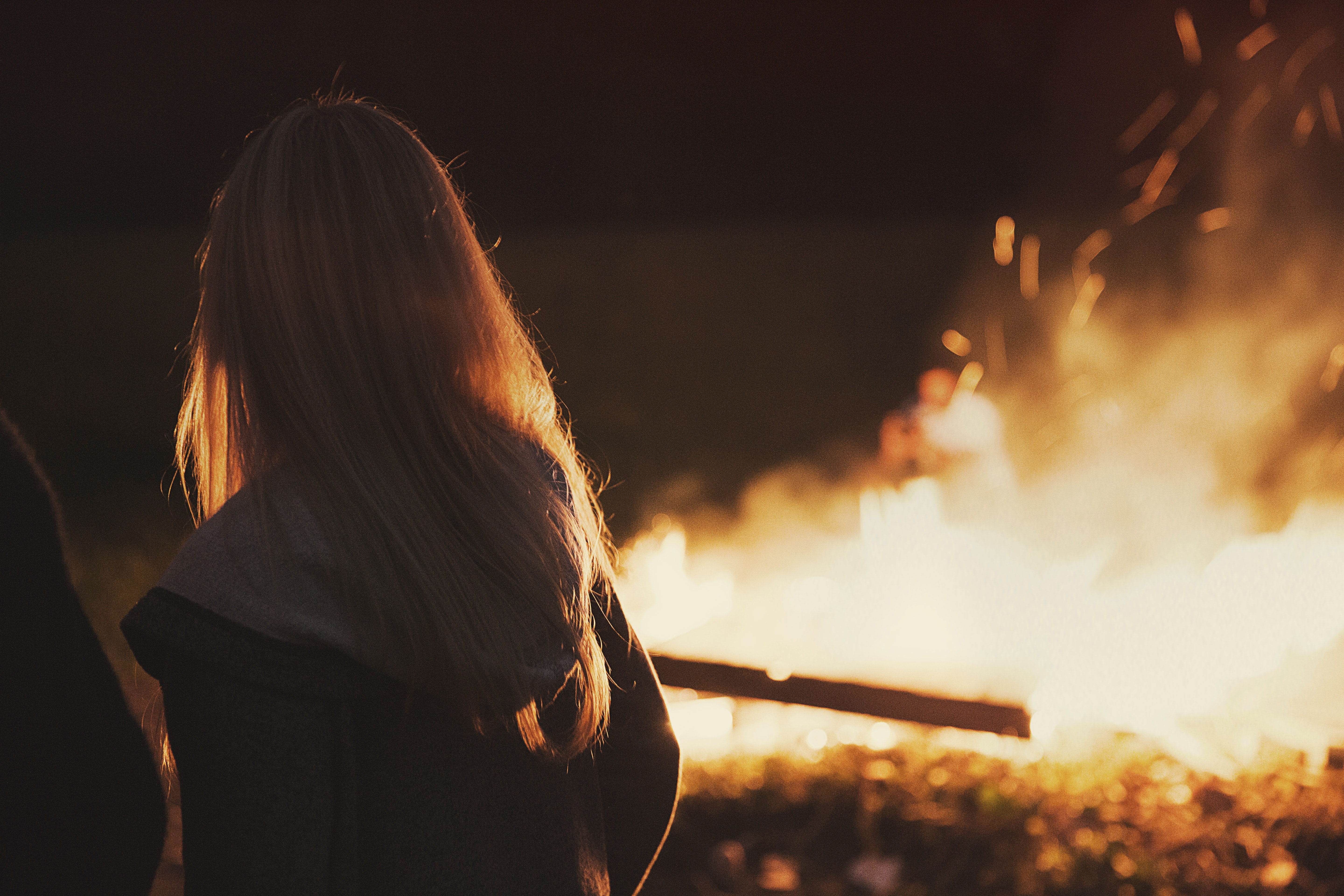 Blonde female captured watching a burning campfire.