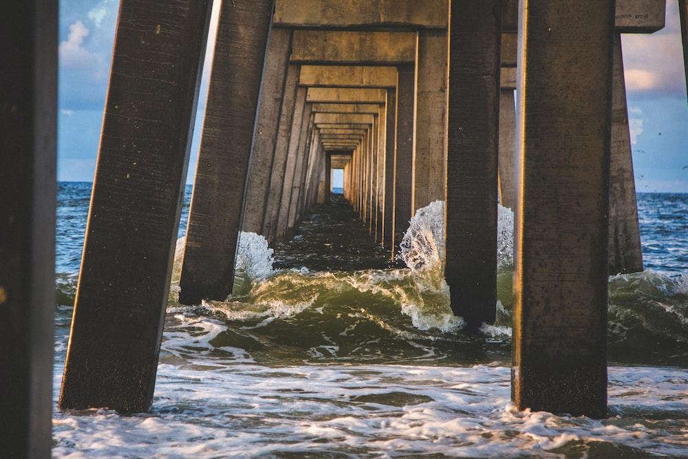sea waves under brown concrete dock at daytime