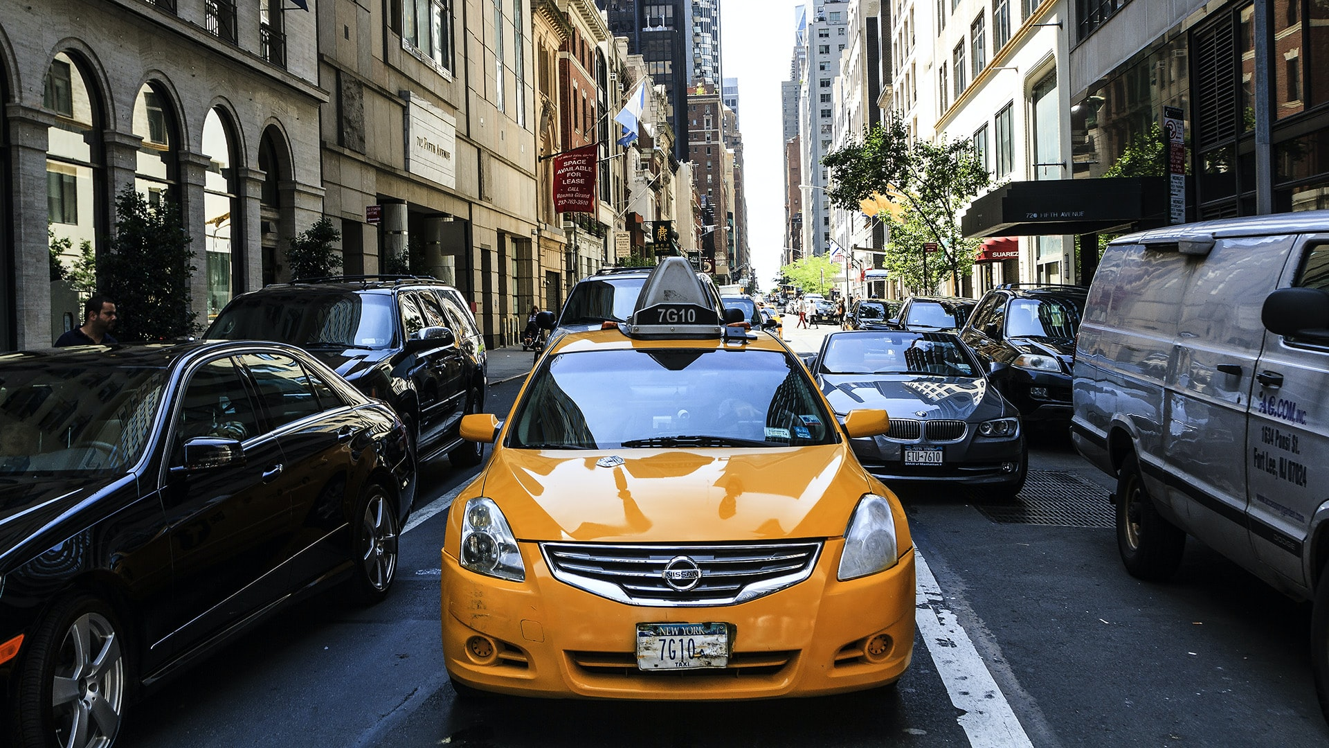 A yellow taxi driving down a busy New York City street