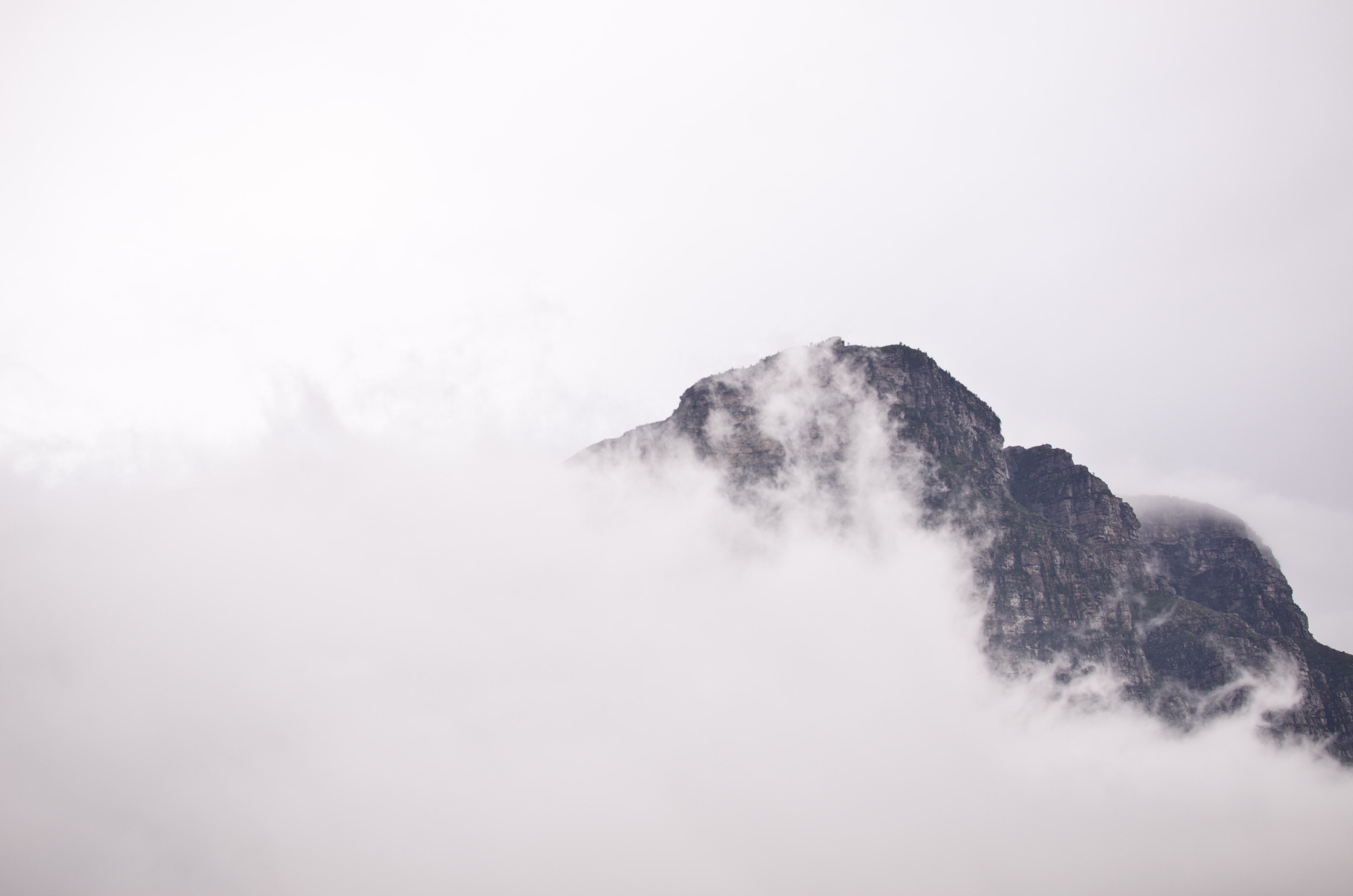 Peak of Table Mountains peek through white mist