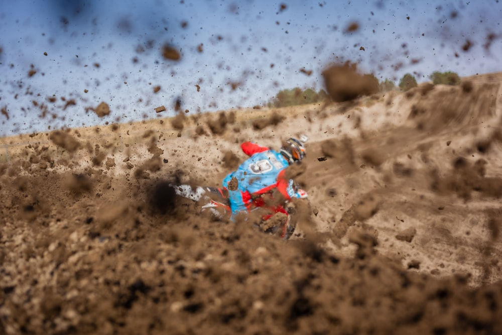 selective focus photography of man riding motorcycle on dirt road
