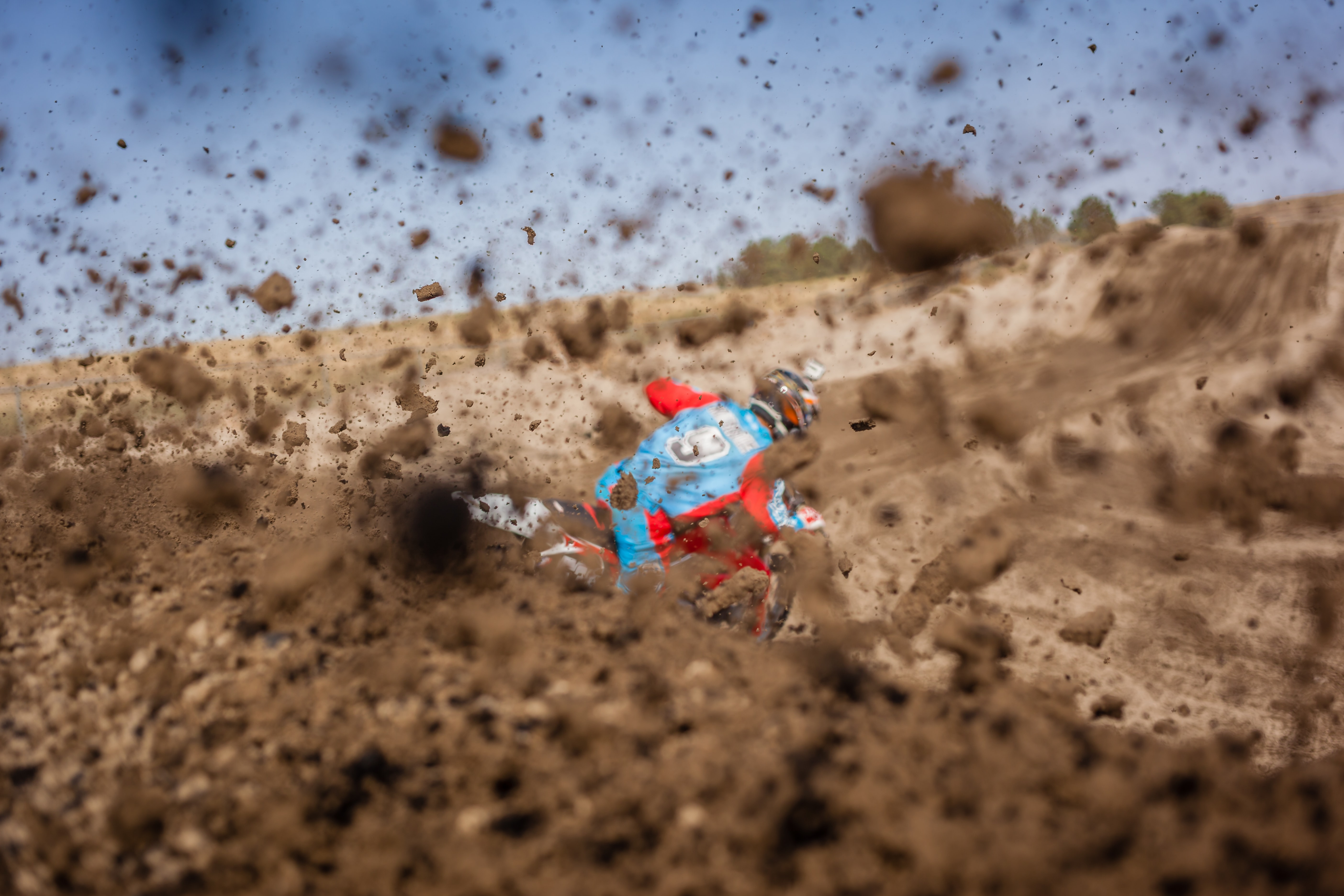 A motorcyclist riding a motorcycle and throwing up dirt and mud with the tires on a track