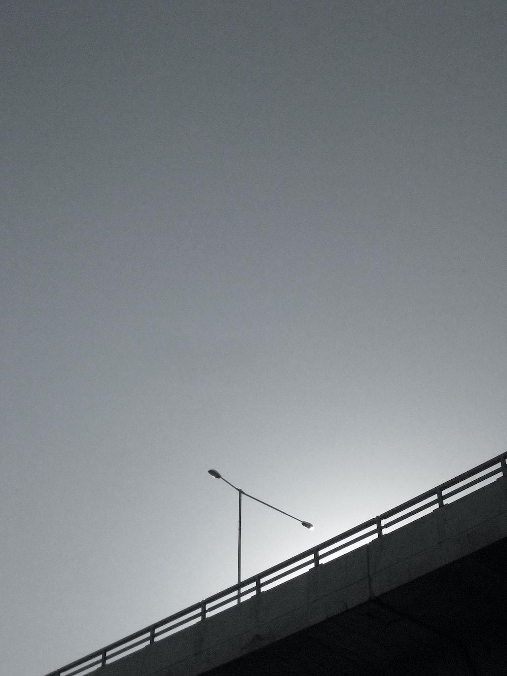 grayscale photo of bridge with postl ight