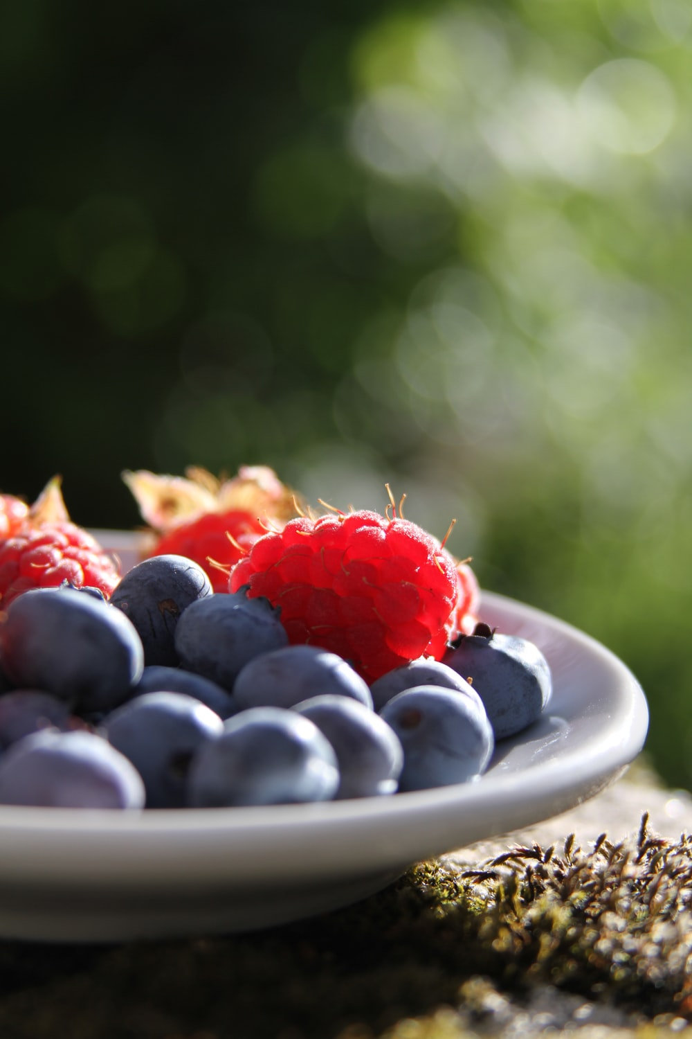 selective focus of blueberries and raspberries on bowl