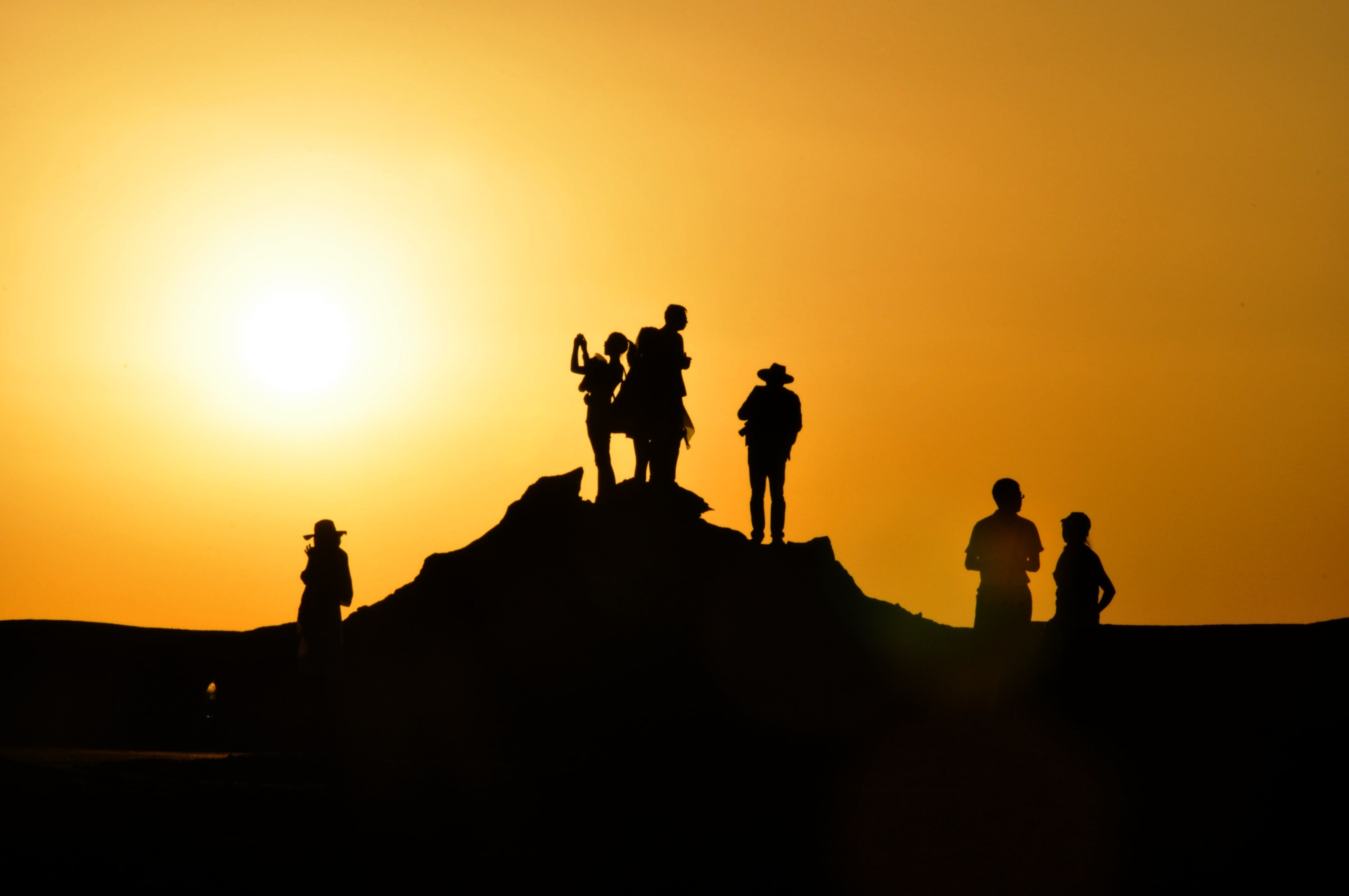 Silhouettes of hikers atop a hillside at sunset