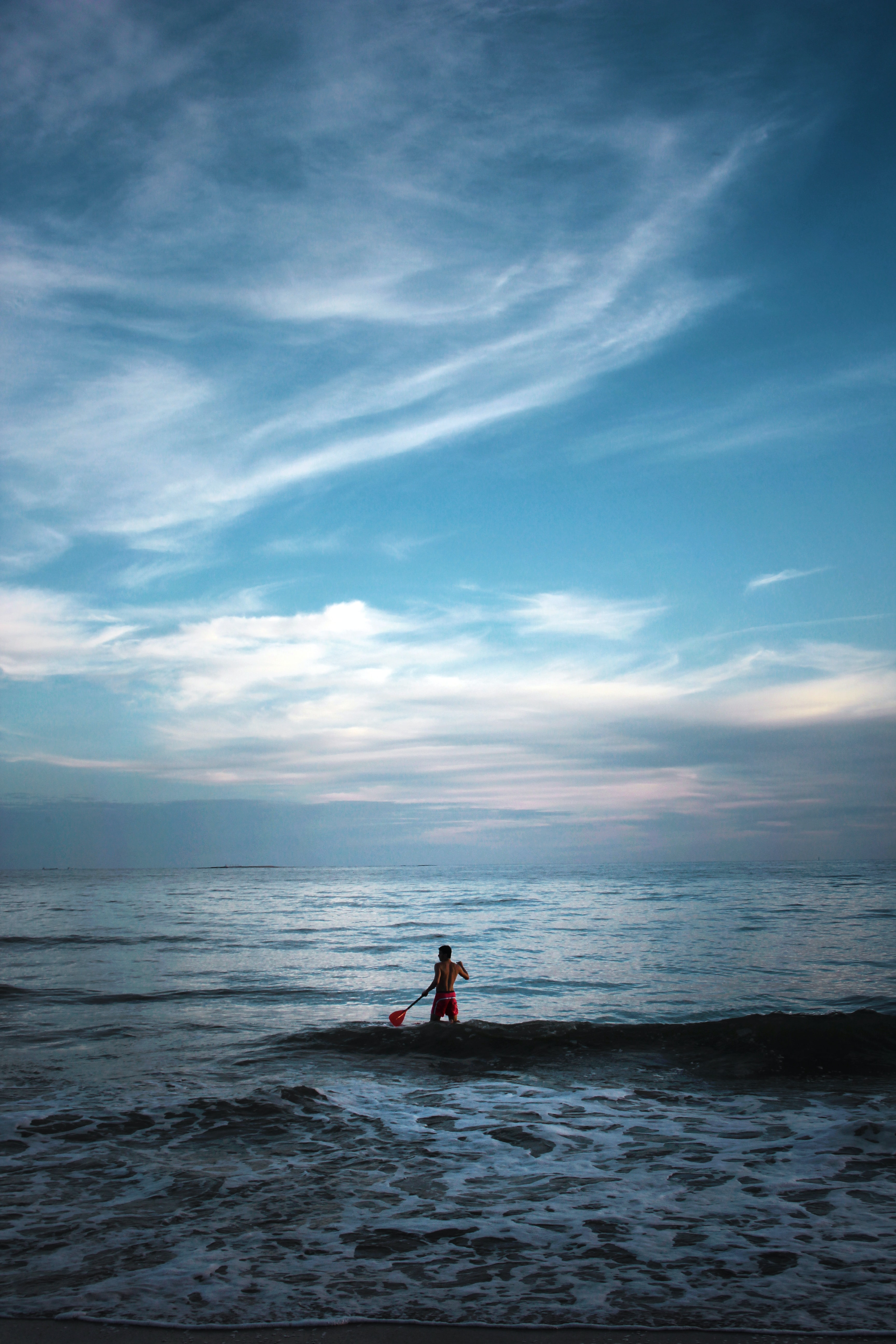 A paddleboarder on a calm sea, beneath a blue dusky evening sky