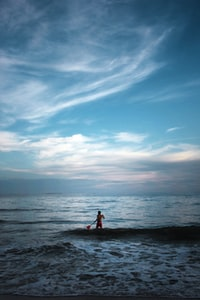man standing on body of water holding paddle